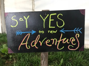 "a chalk sign ""say yes to new adventures"""
