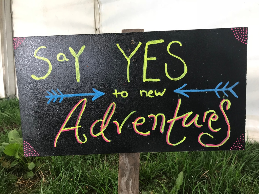 "A chalk board sign ""say YES to new Adventures"""