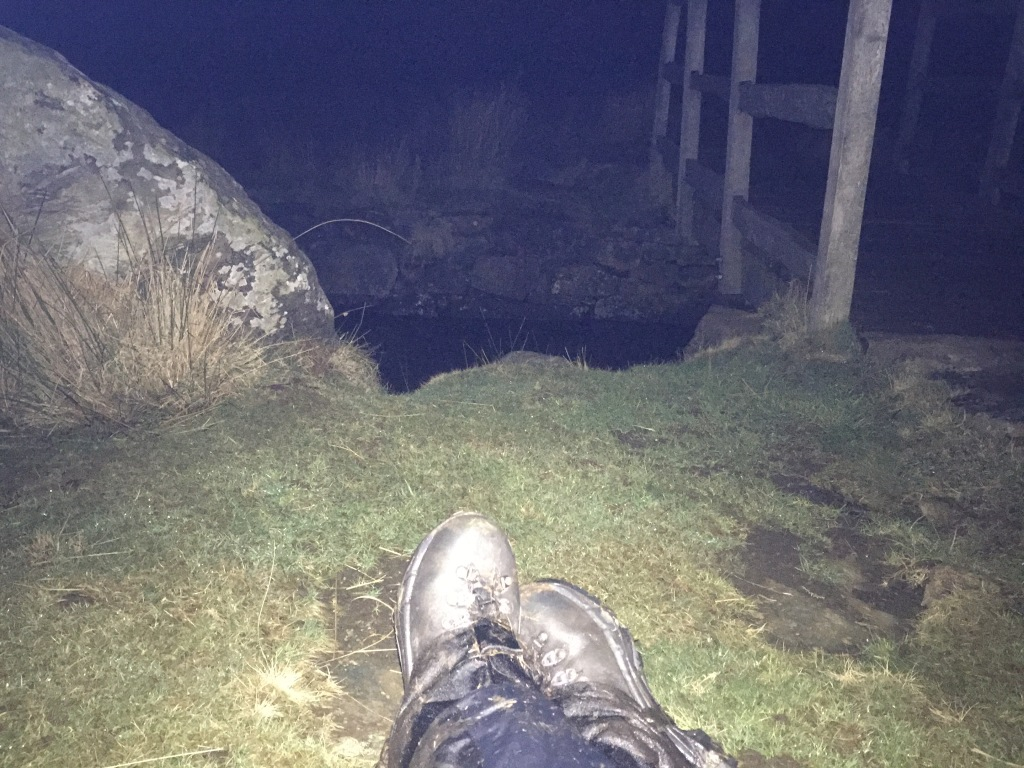 A headtorch lights up boots by a wooden bridge