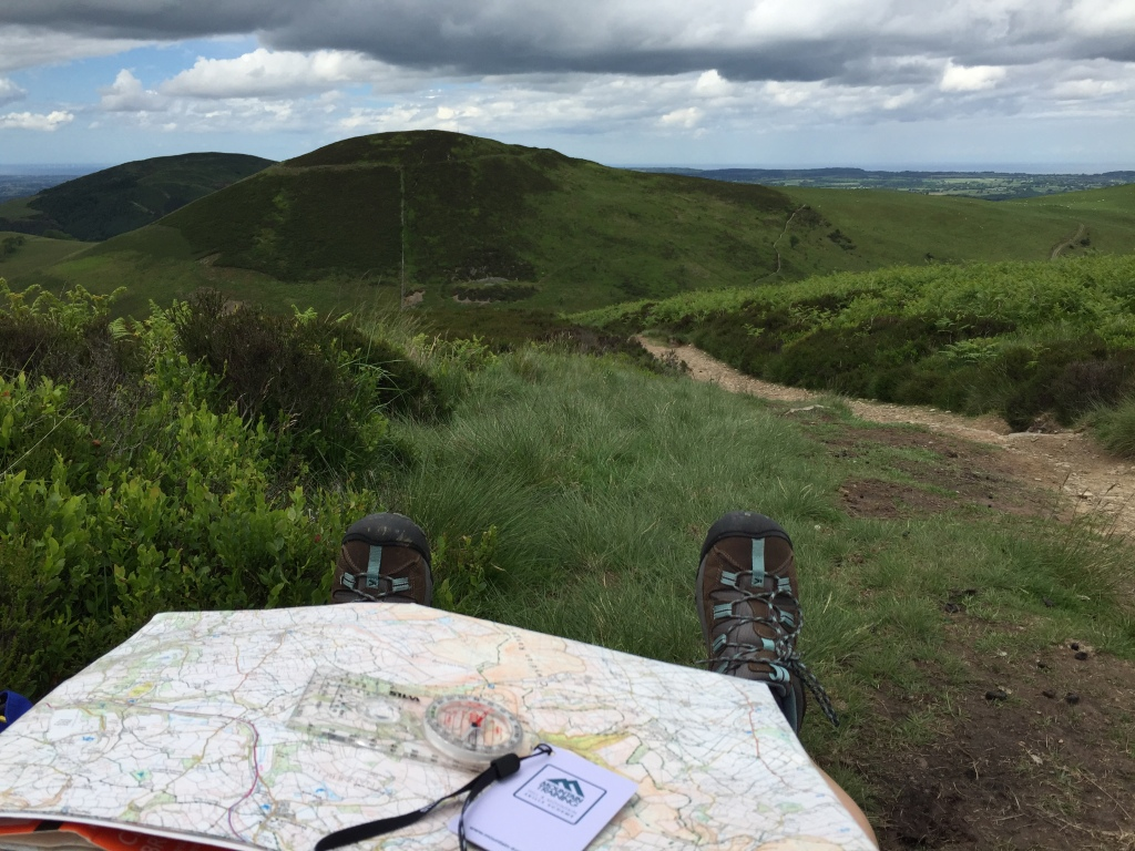 A map and compass on a walkers lap, looking towards a range of hills