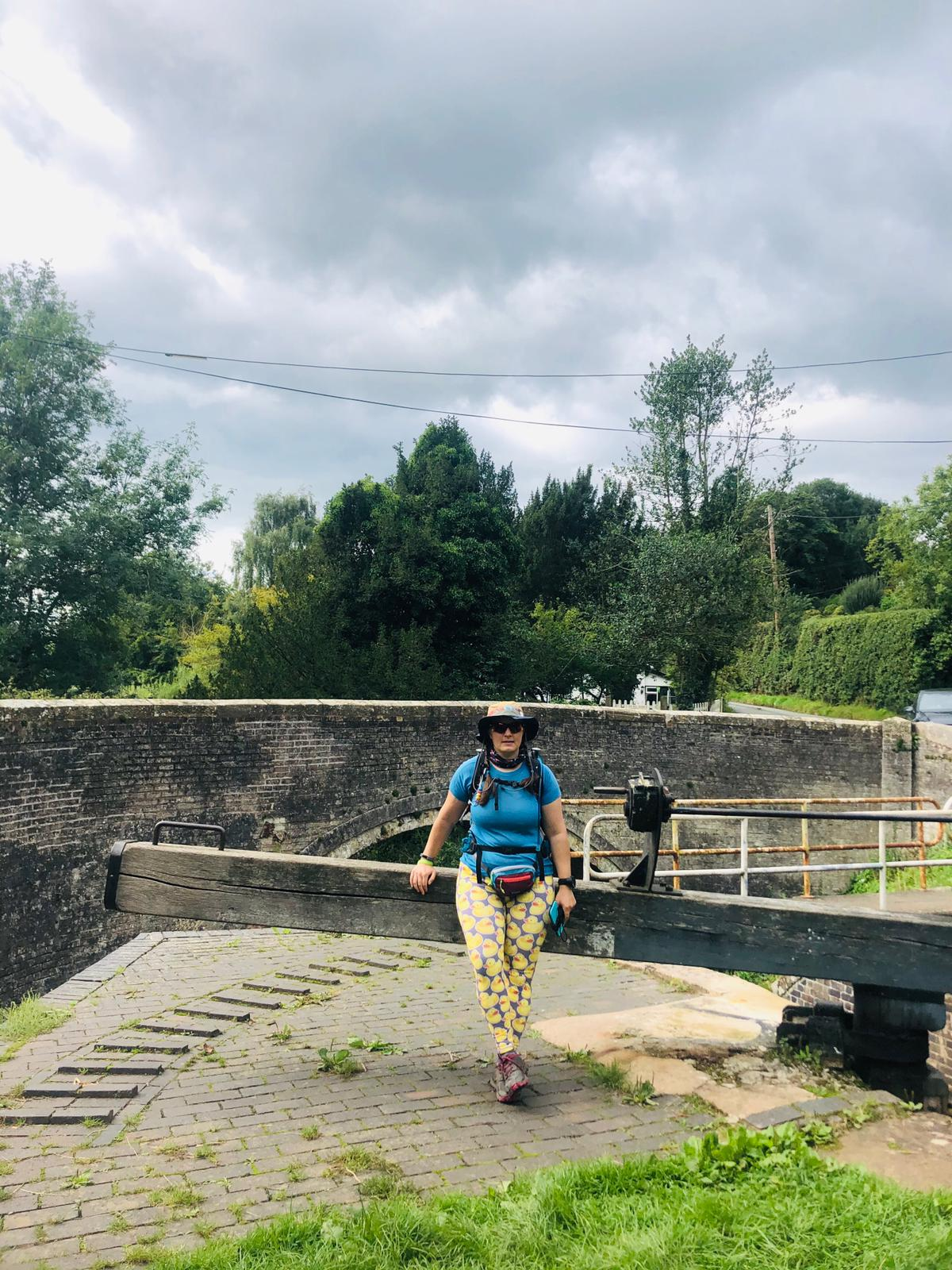 A woman in walking kit sitting on a canal lock gate