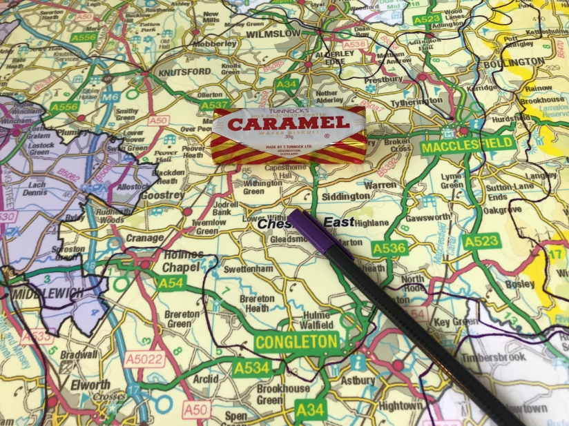A pen and Tunnock Caramel wafer on a map