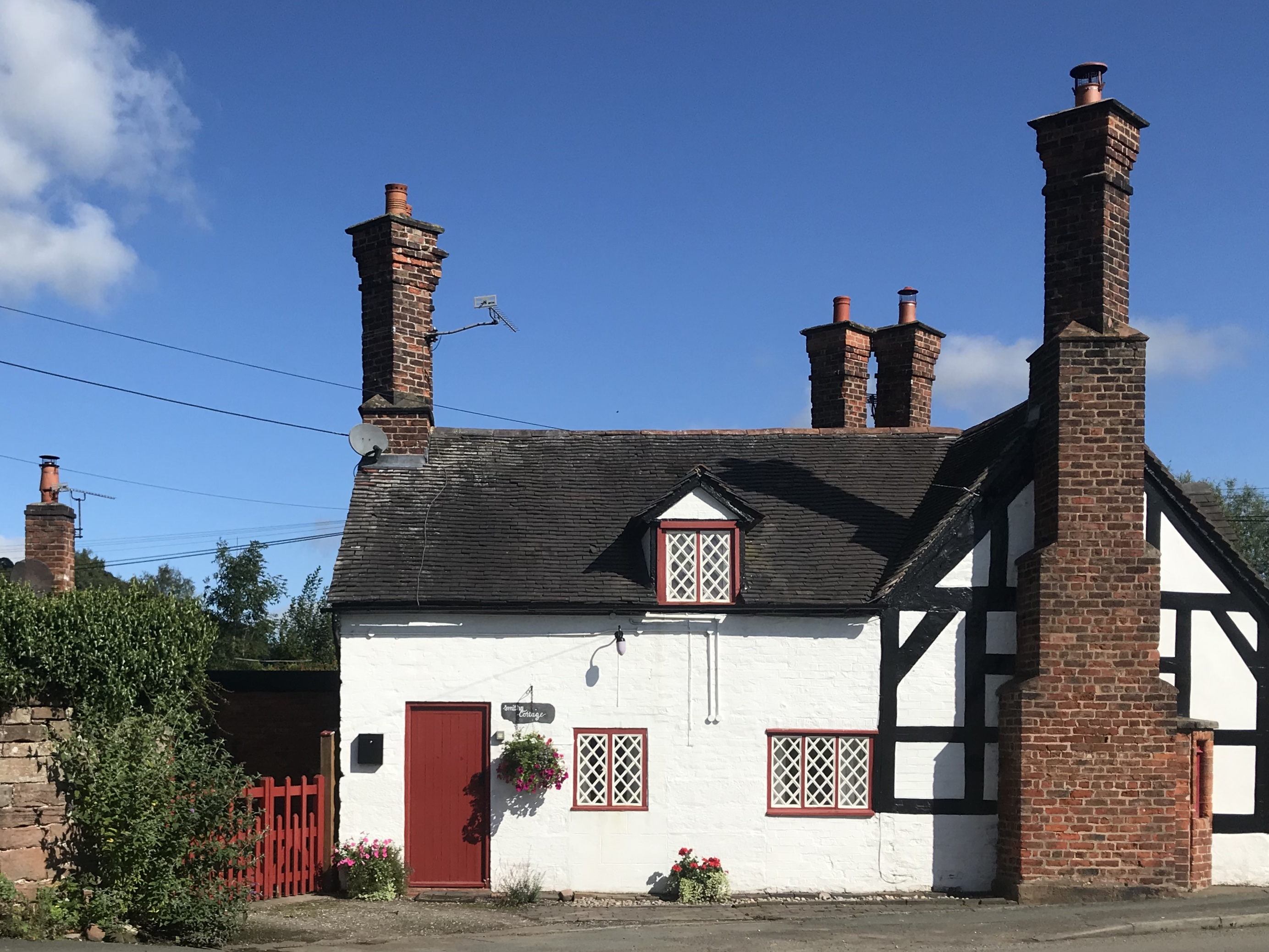 A small black and white cottage with large red brick chimneys