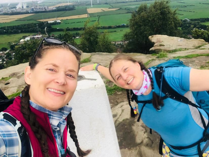 A selfie of two women in walking kit next to a trig on a hill