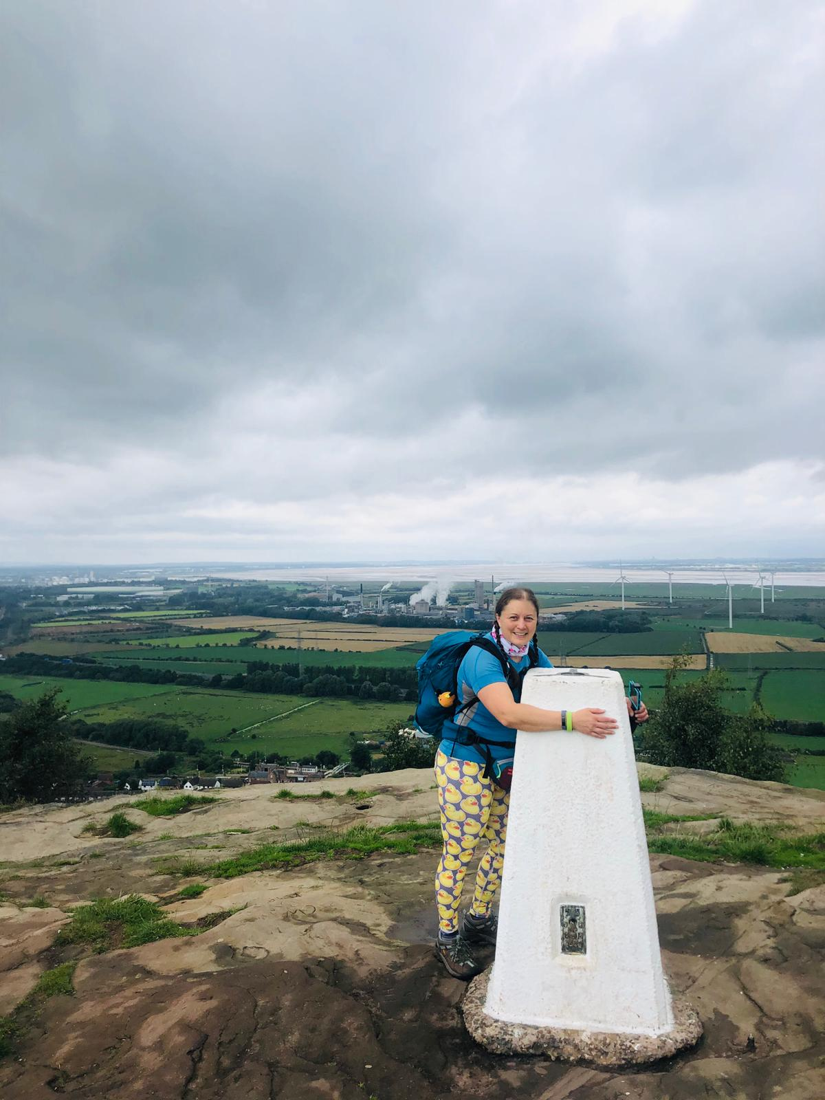 a woman in walking kit hugging a trig on a hill overlooking a windfarm
