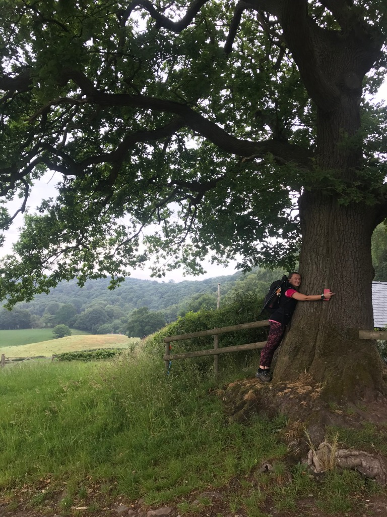 A woman in walking kit hugging a large oak tree