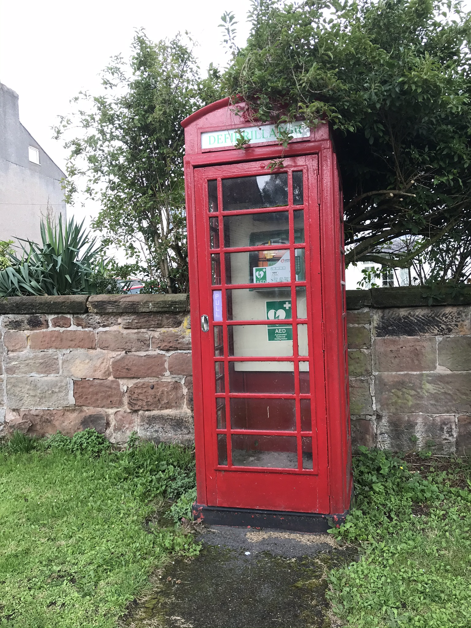An old red telephone box containing an automated external defibrilator