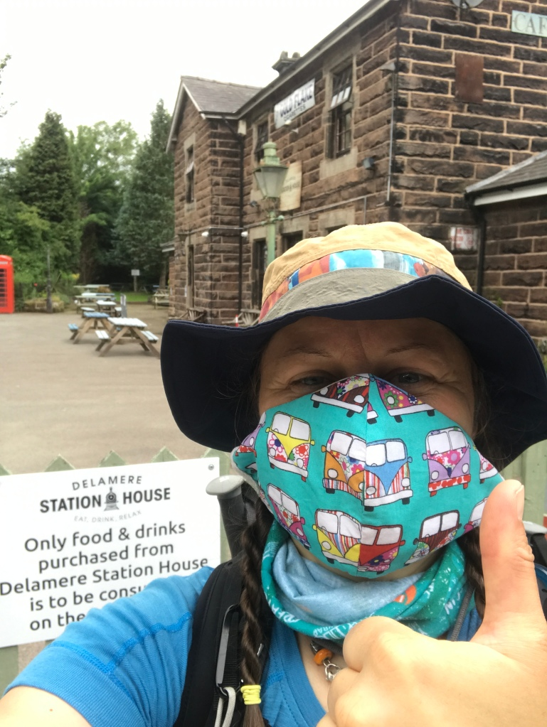 A selfie of a woman wearing a mask outside a stone building, giving a thumbs up sign