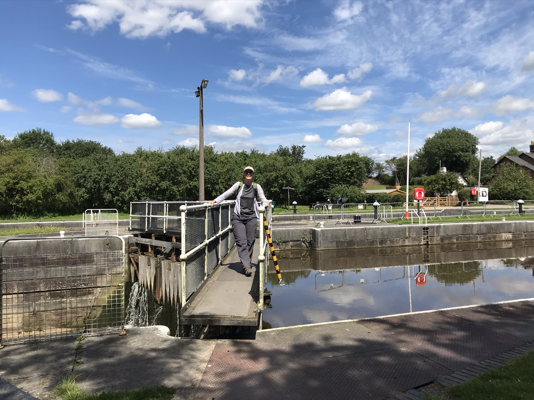 A walker stands on top of very big lock gates