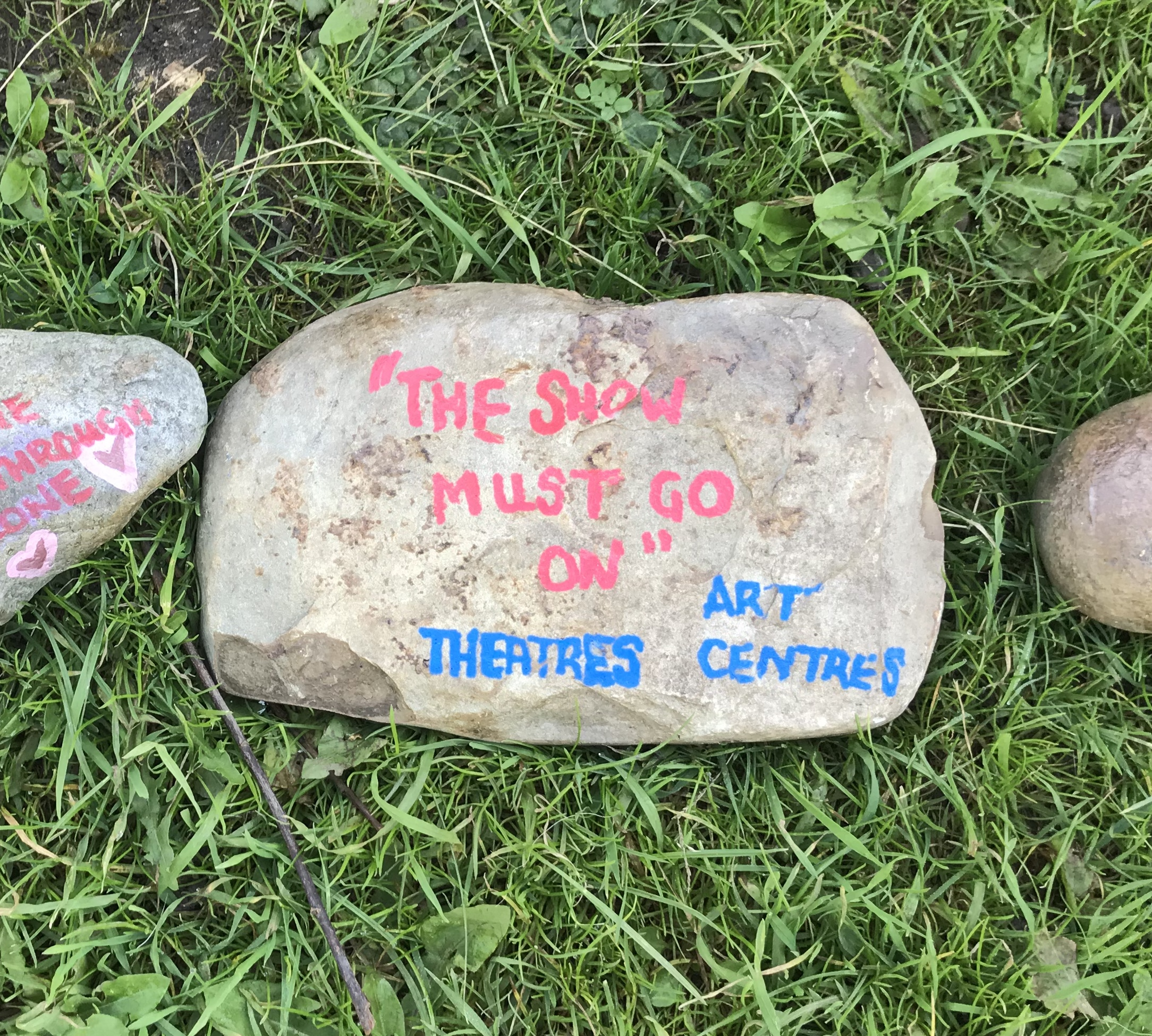 "a stone with ""the show must go on"" ""Theatres"" and ""Art centres"" painted on it."