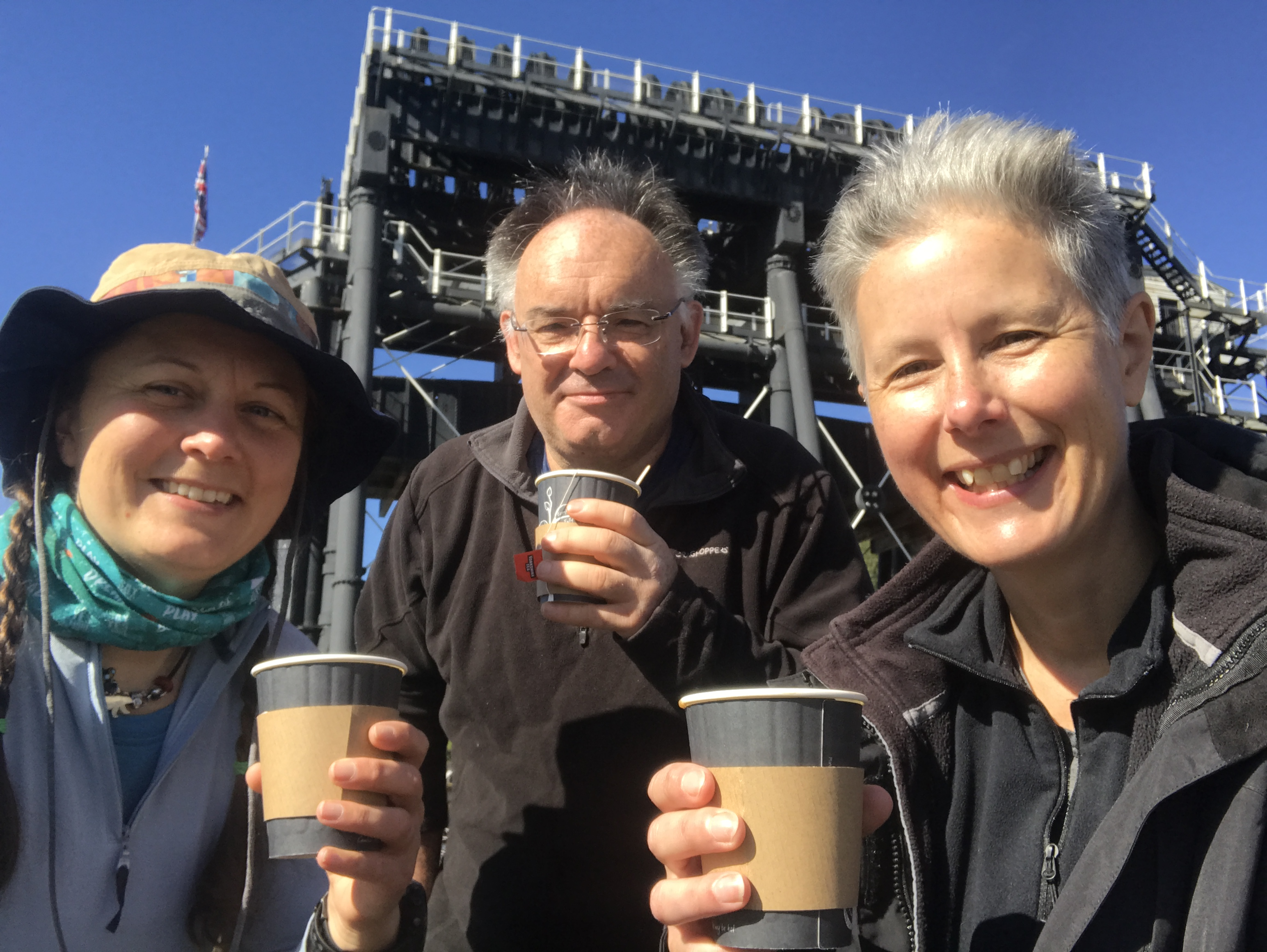 a selfie of three people with paper cups of tea in front of the Anderton boat lift.