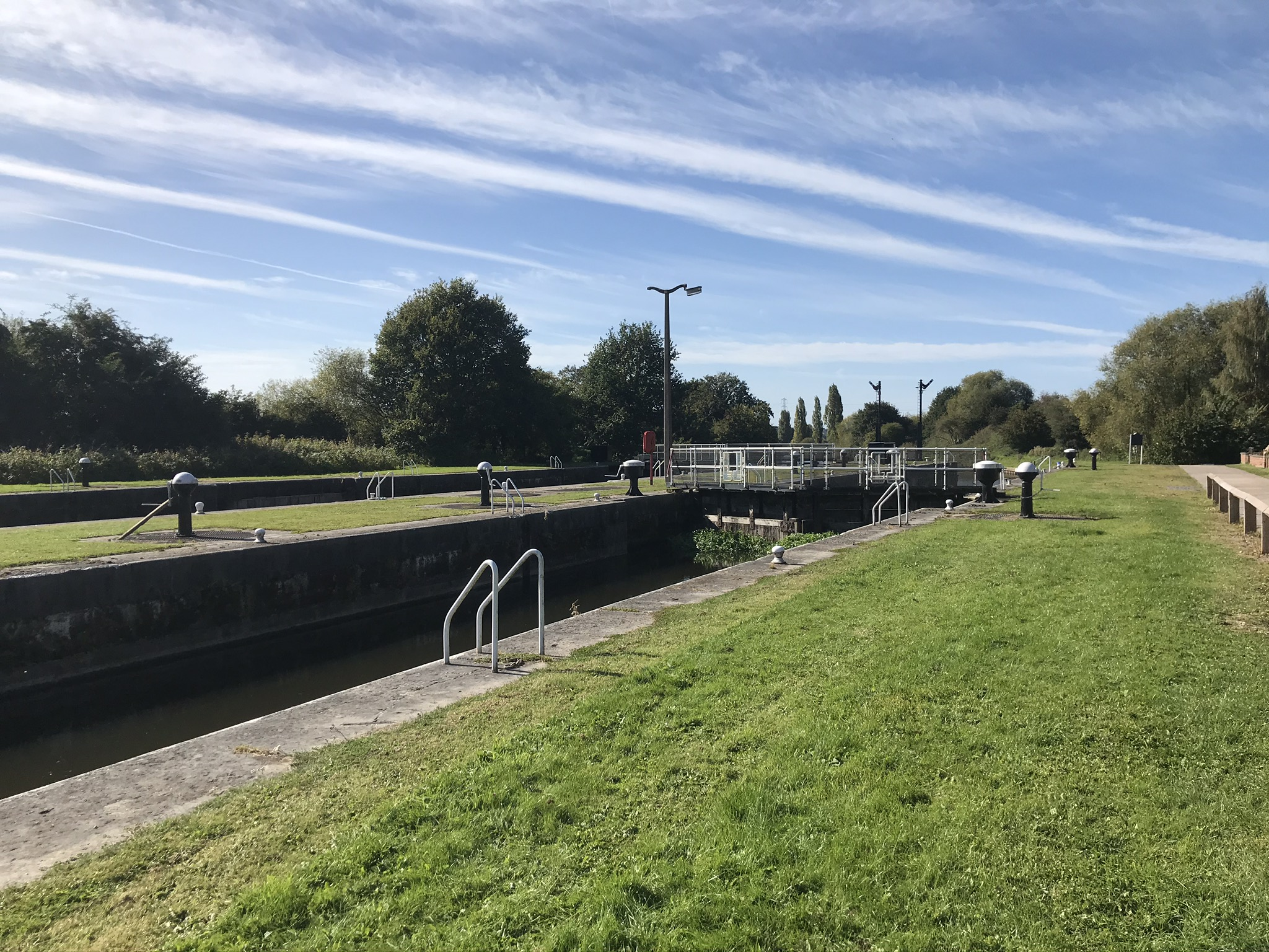 A lock gate with blue skies and mown grass banks