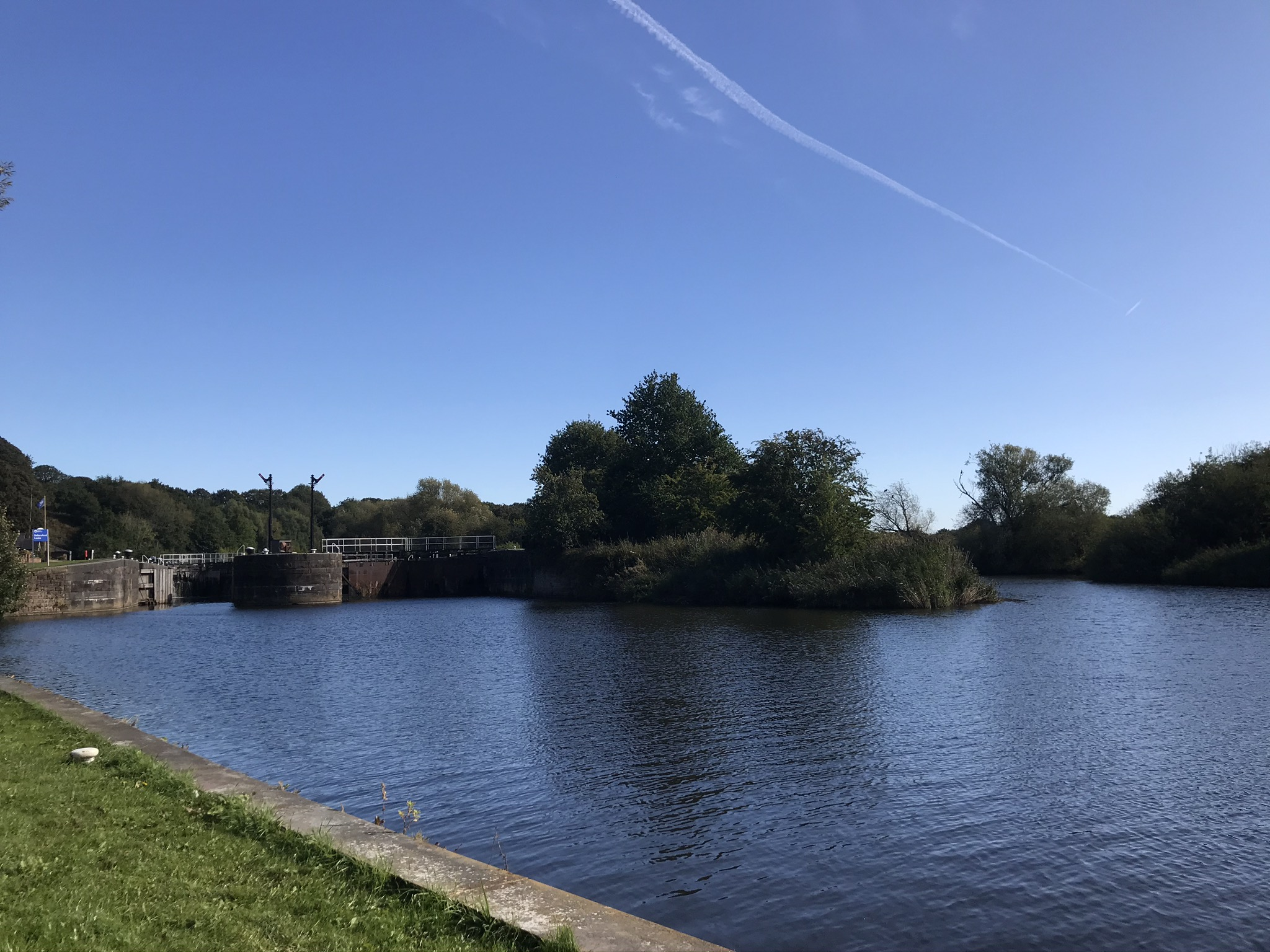 A river lock and the river reflecting a blue sky with trees on an island