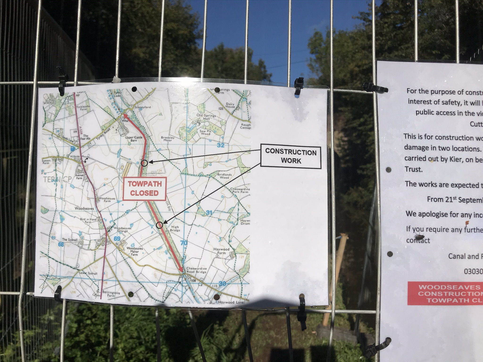 A construction work sign tied to a wire fence. The sign is a map showing a section of the footpath is closed with two areas of construction.