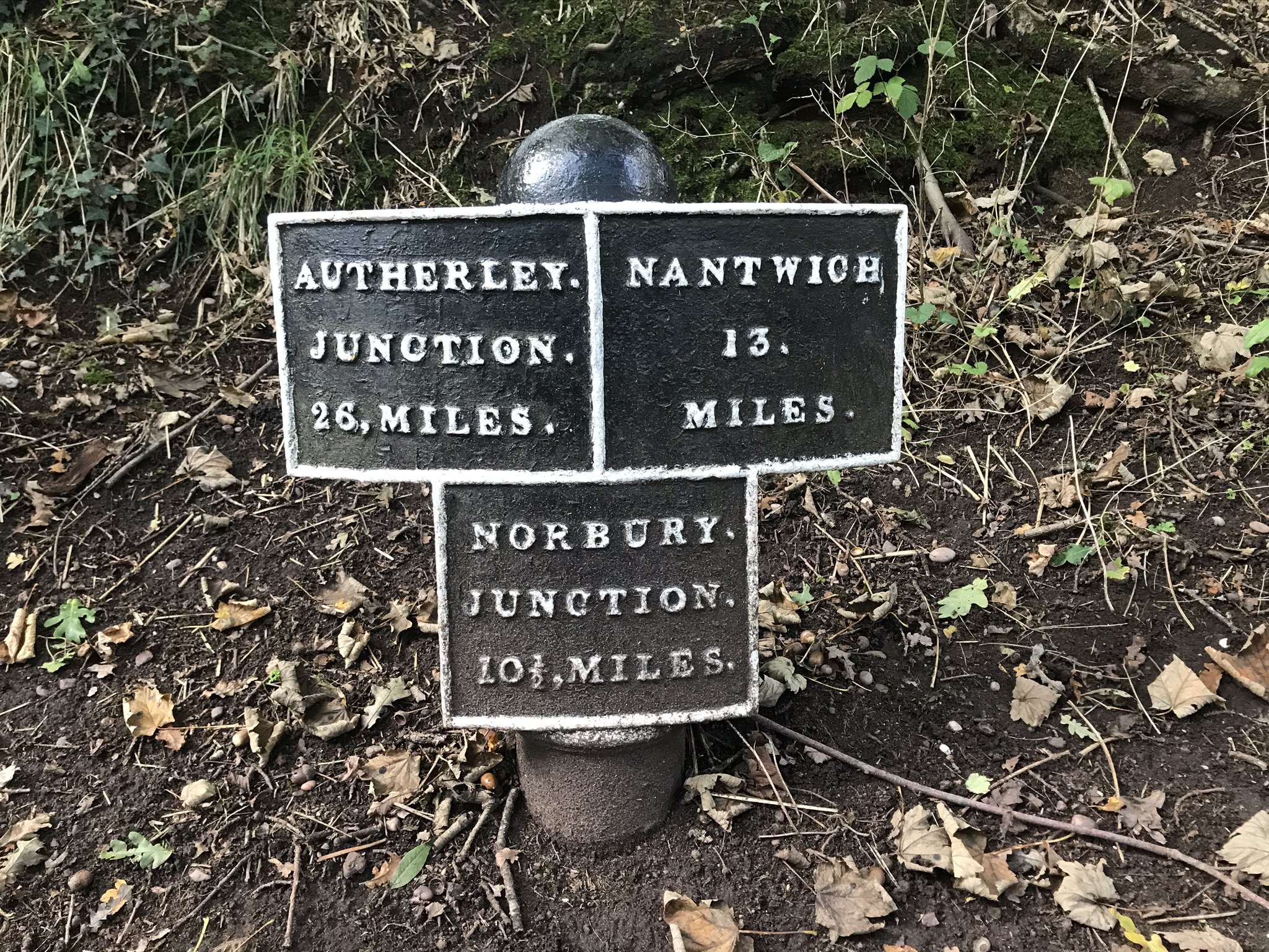 "A black metal sign made of three squares with white writing in a soil verge. The top left sign is ""Autherley Junction 26 miles"", the top right is ""Nantwich 13 miles"" and the middle bottom is ""Norbury junction 10 1/2 miles"""