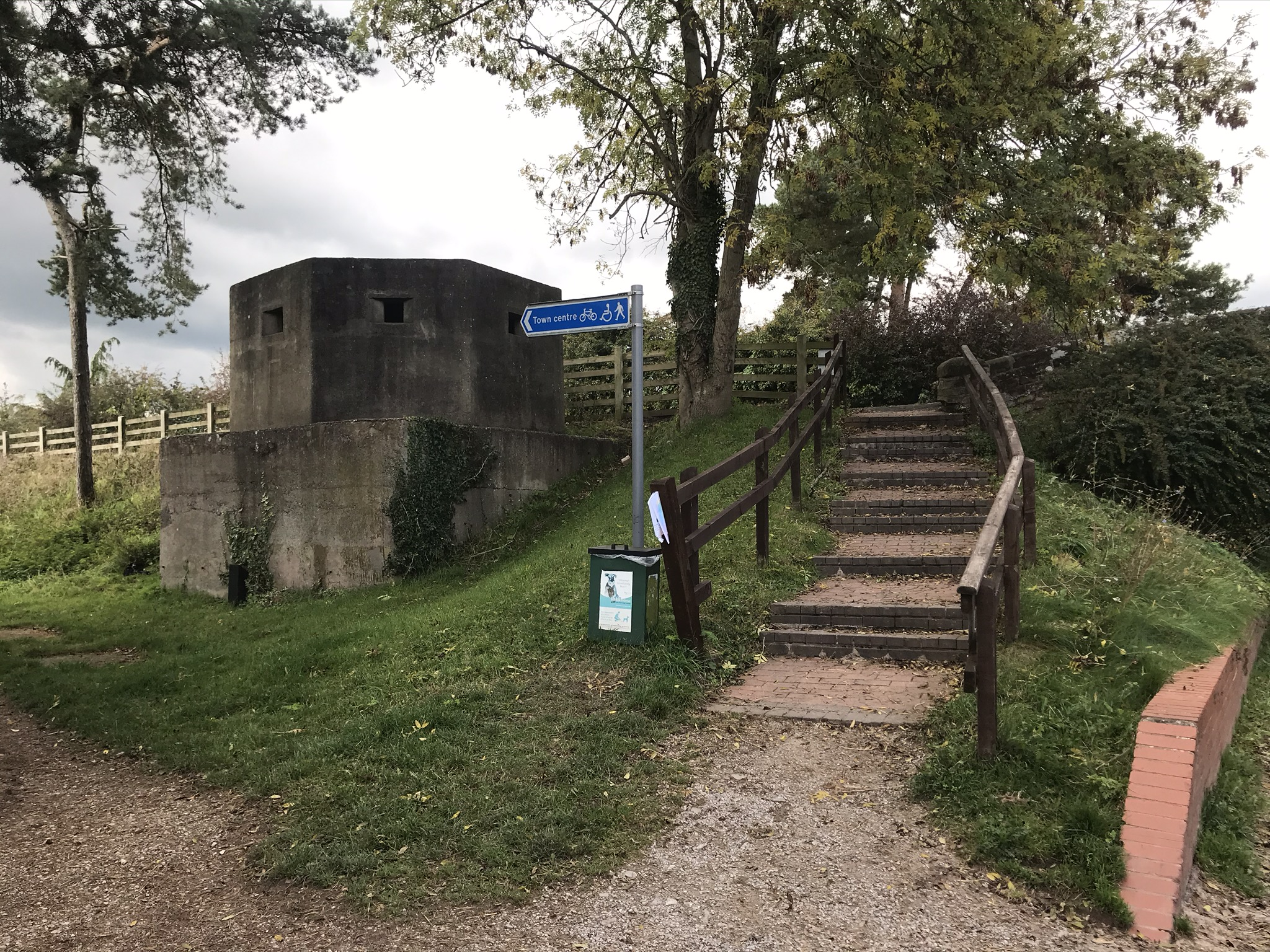 A concrete WW2 pillbox next to brick steps and a blue sign pointing towards the town centre