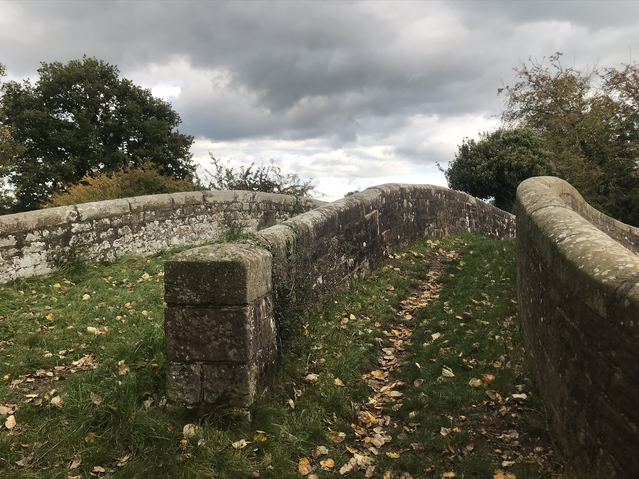 A view from the end of a canal bridge, there is a stone wall dividing the path on the bridge into two paths.
