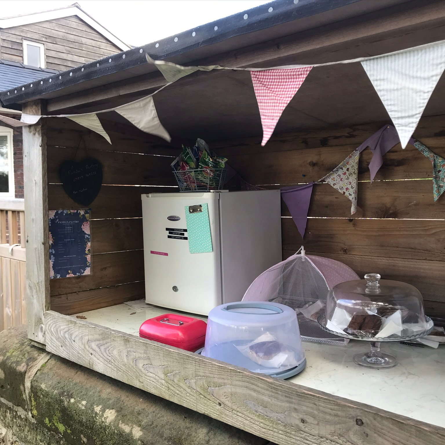 A timber shelter with pastel coloured bunting. There is cake under covers, a fridge and a red cash box.