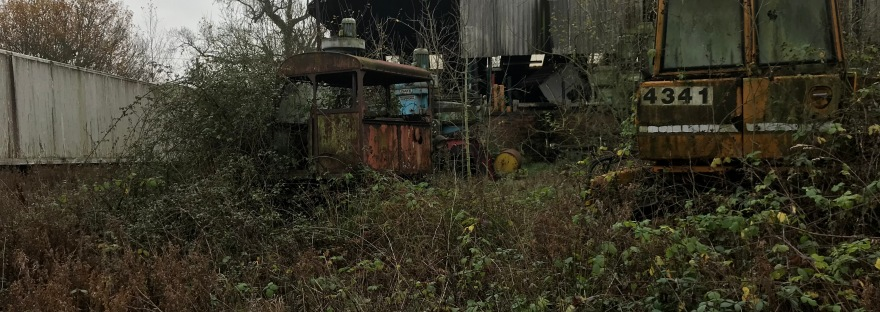 A rusty corrugated steel barn with rusty agricultural and railway maintenance machinery, all heavily overgrown with thick brambles