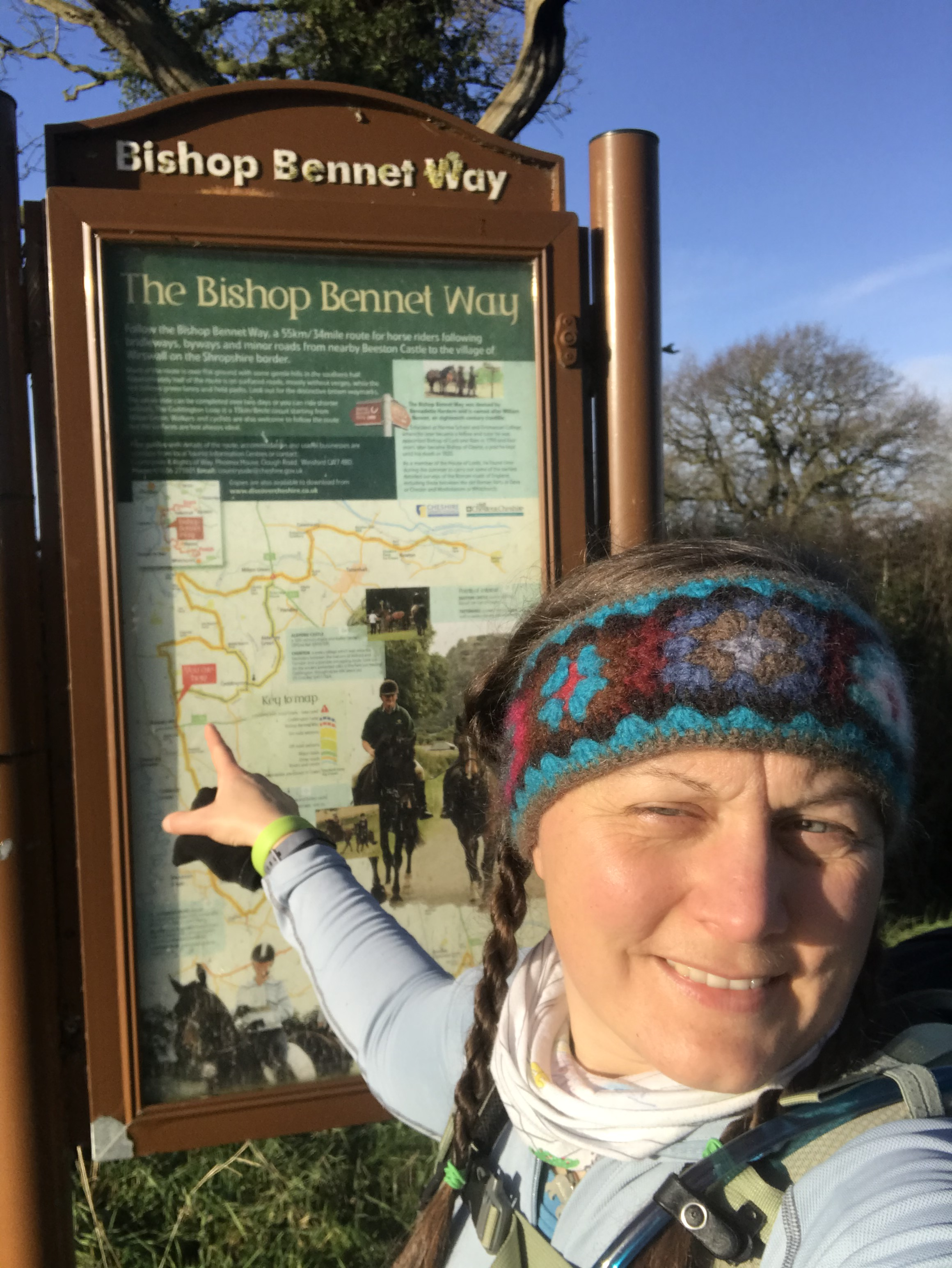a woman wearing a knitted headbad pointing at a location on a large information board map