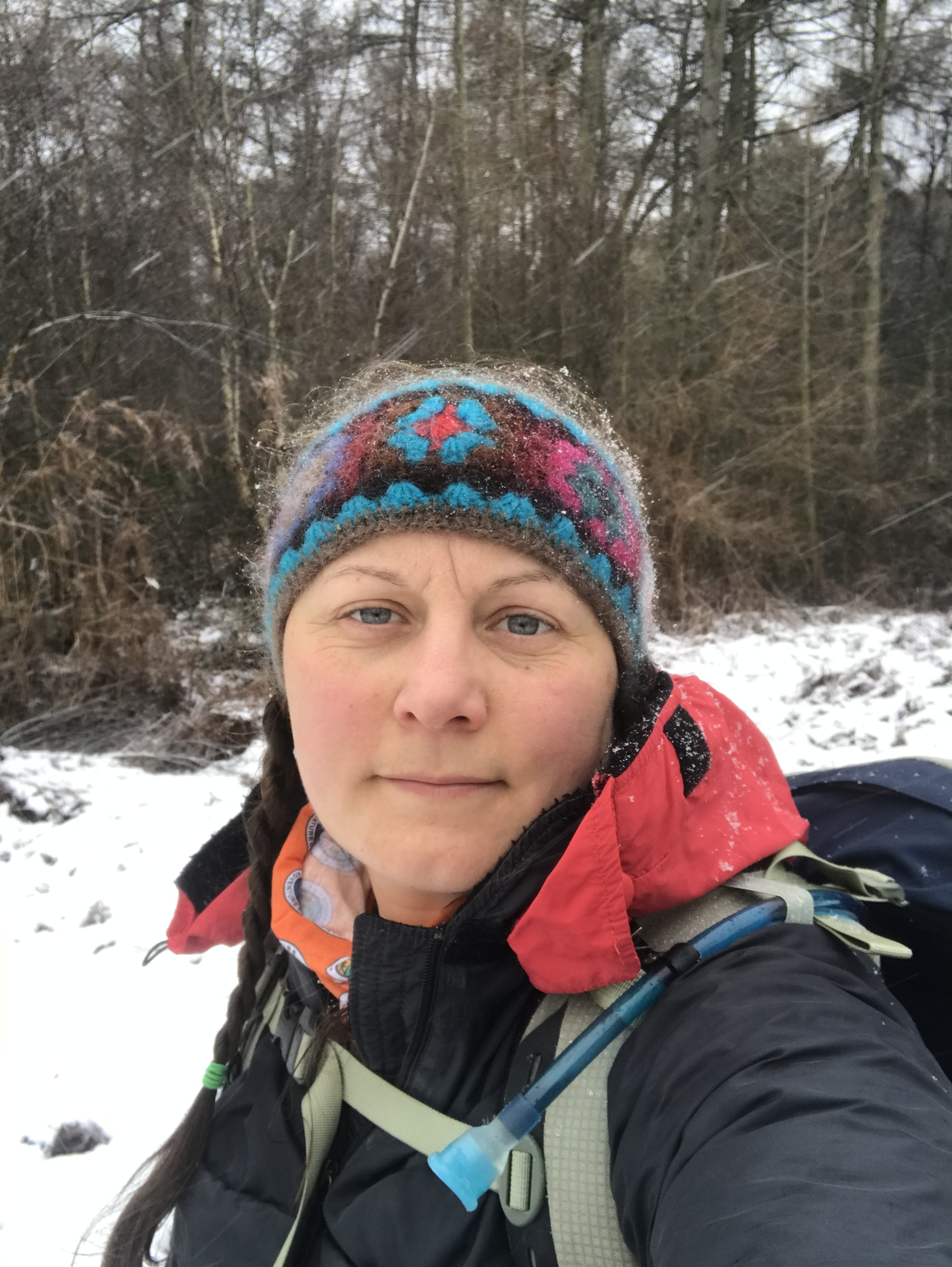 A selfie, wearing winter walking gear. The ground is covered in snow with wood in the background.