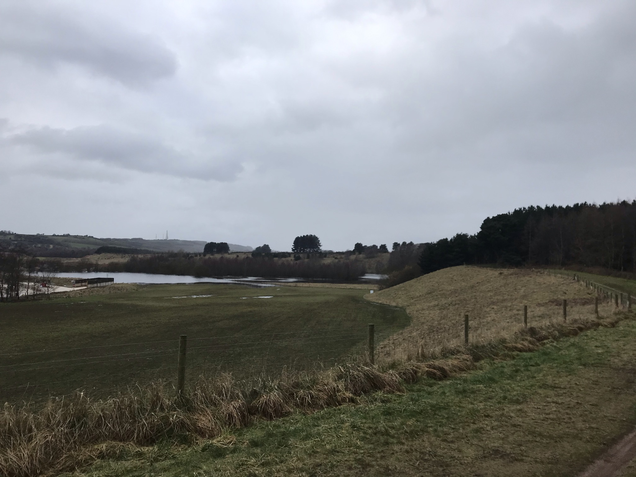 Grass banks with a lake in the distance. A fence run along the top of the bank with woods to the right. In the distance there are hills with a mast on top