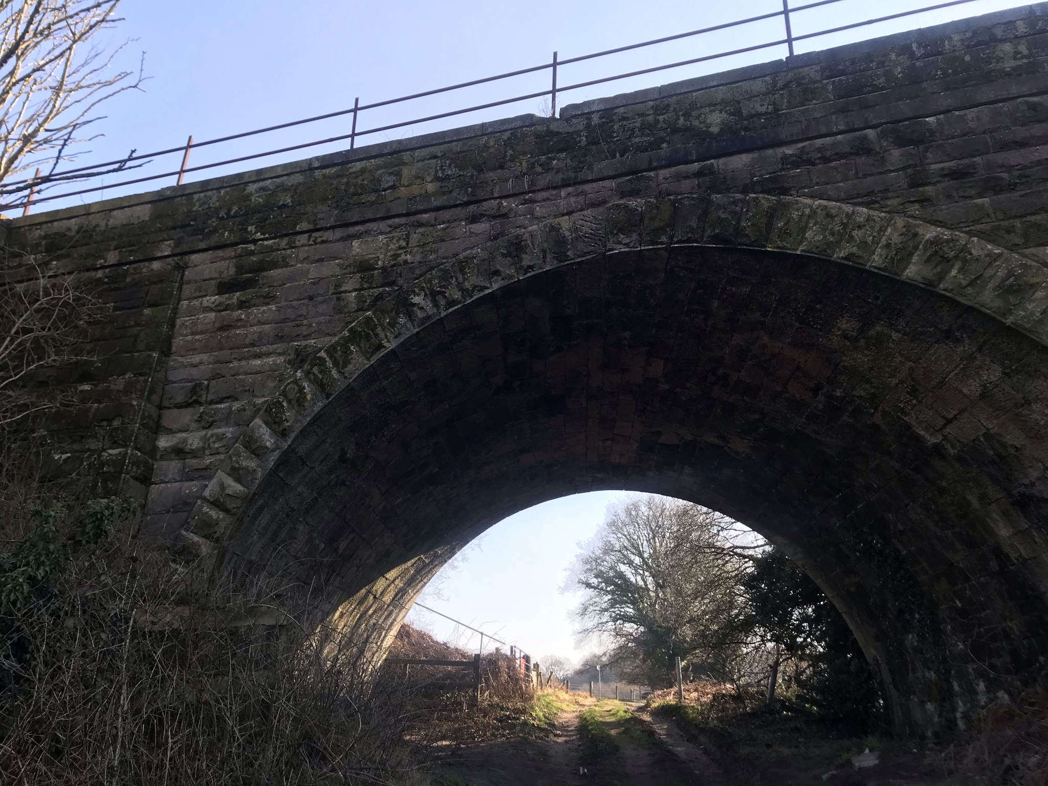 Looking up at a stone arch bridge. There is a rutted track underneath with bare trees in the background
