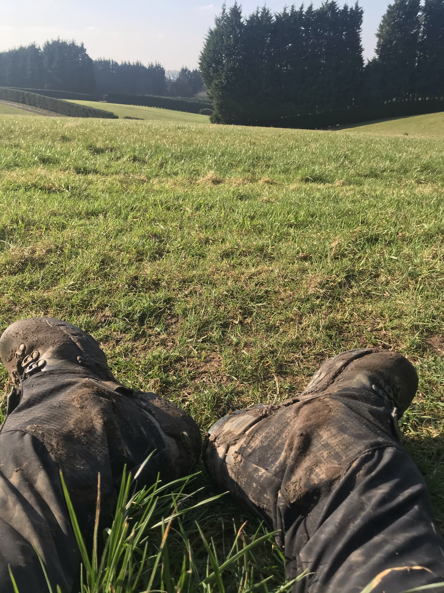 muddy boots of a person sat on the grass. The fields are gently rolling in the background and there are tall thick trees and neat hedges