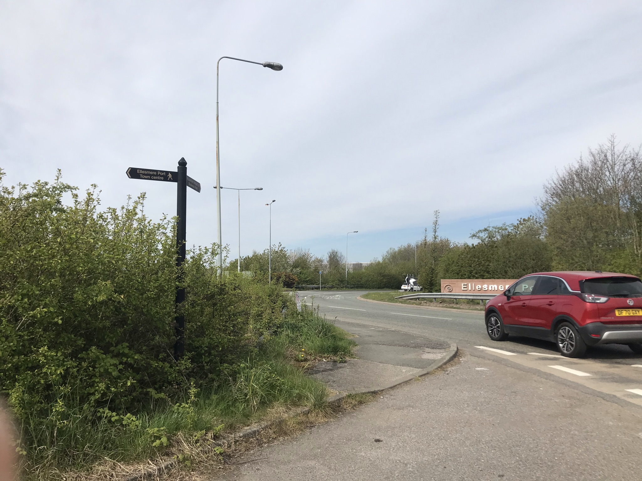A black finger post for a footpath on a busy roundabout