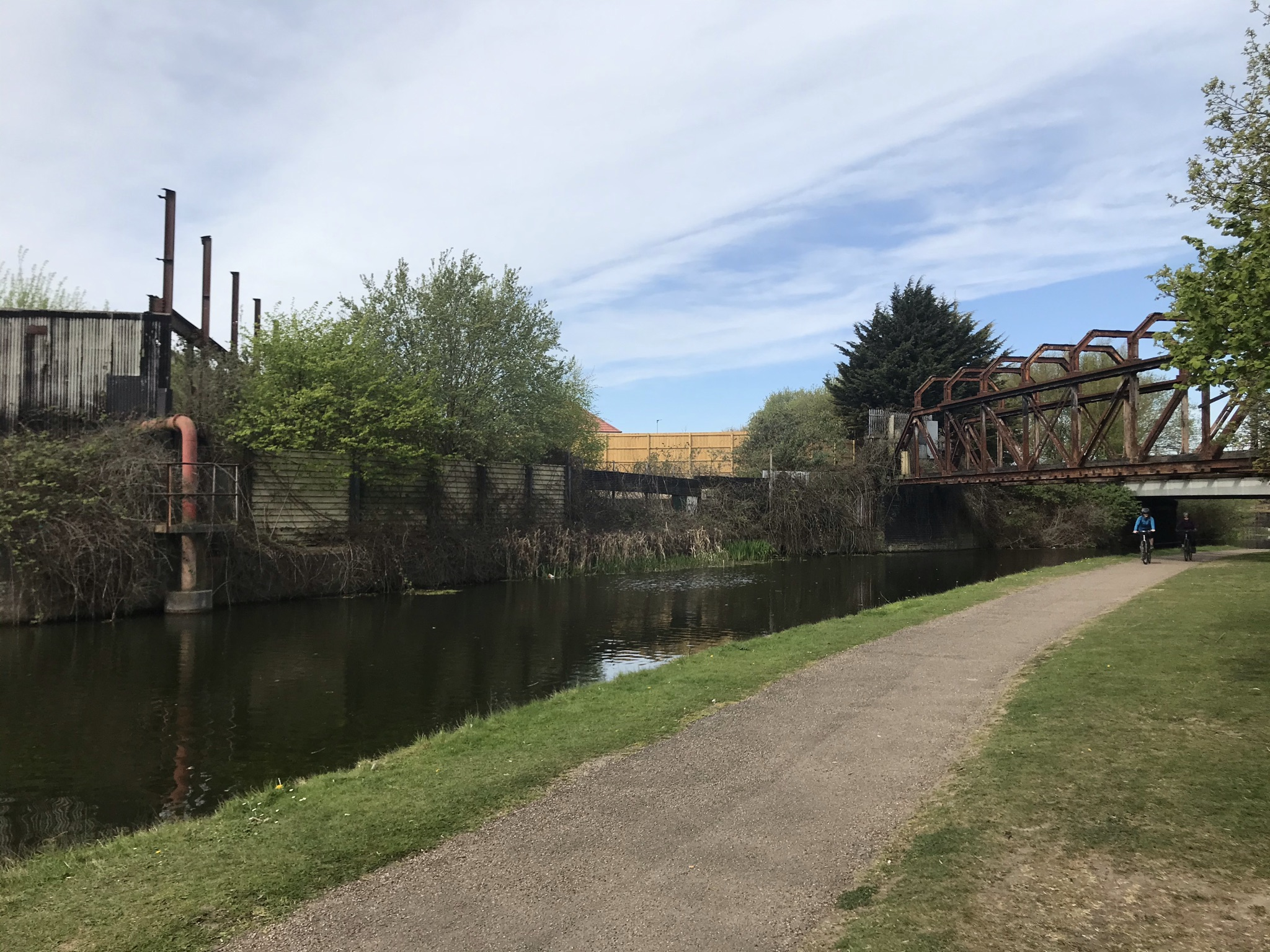 A towpath alongside the canal with a rusty steel frame bridge and dilapidated buildings