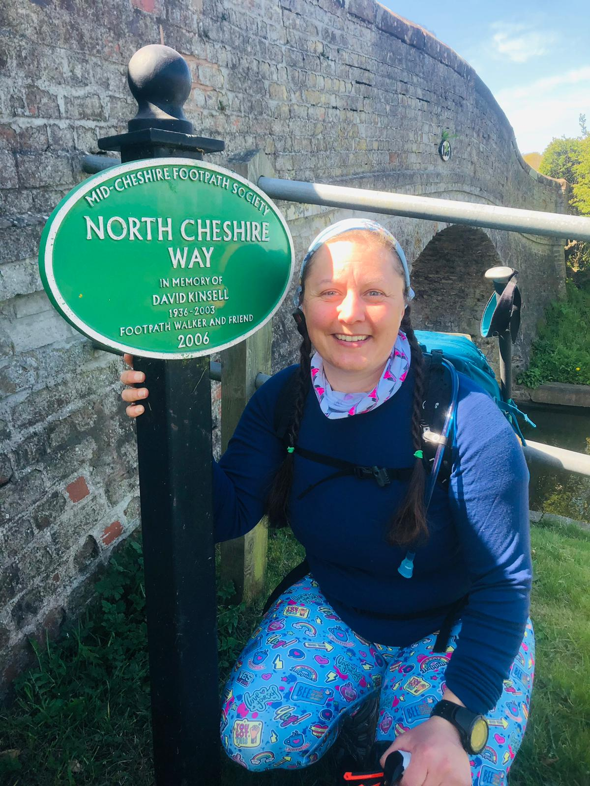 A green cast metal sign for the North Cheshire Way alongside a canal bridge. A woman in walking kit is sat next to it smiling at the camera