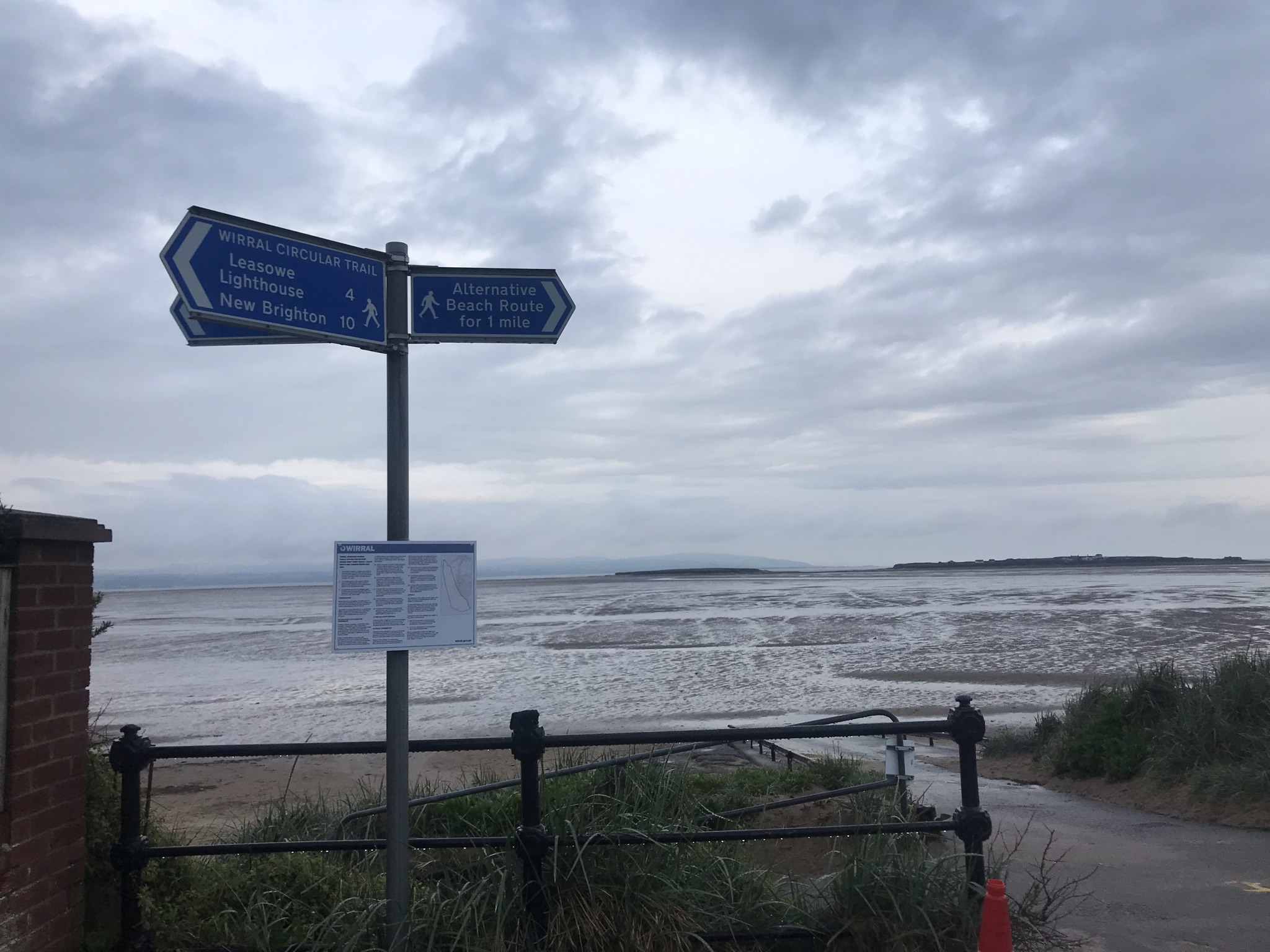 Blue sign post in front a beach. The tide is out and in the distance is hilbre island