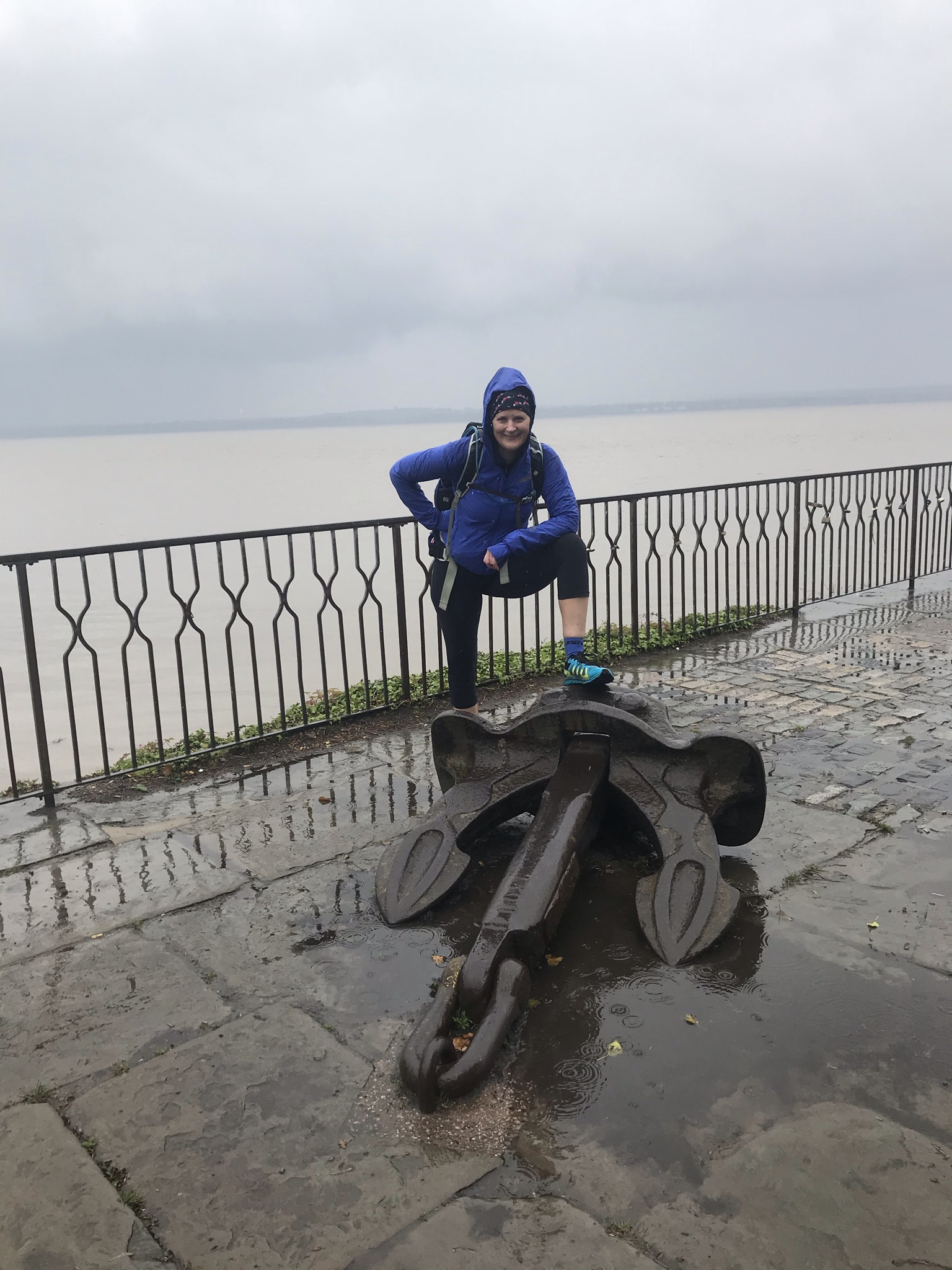 Sarah stands with one foot on an anchor. Behind her the sky is grey and rainy