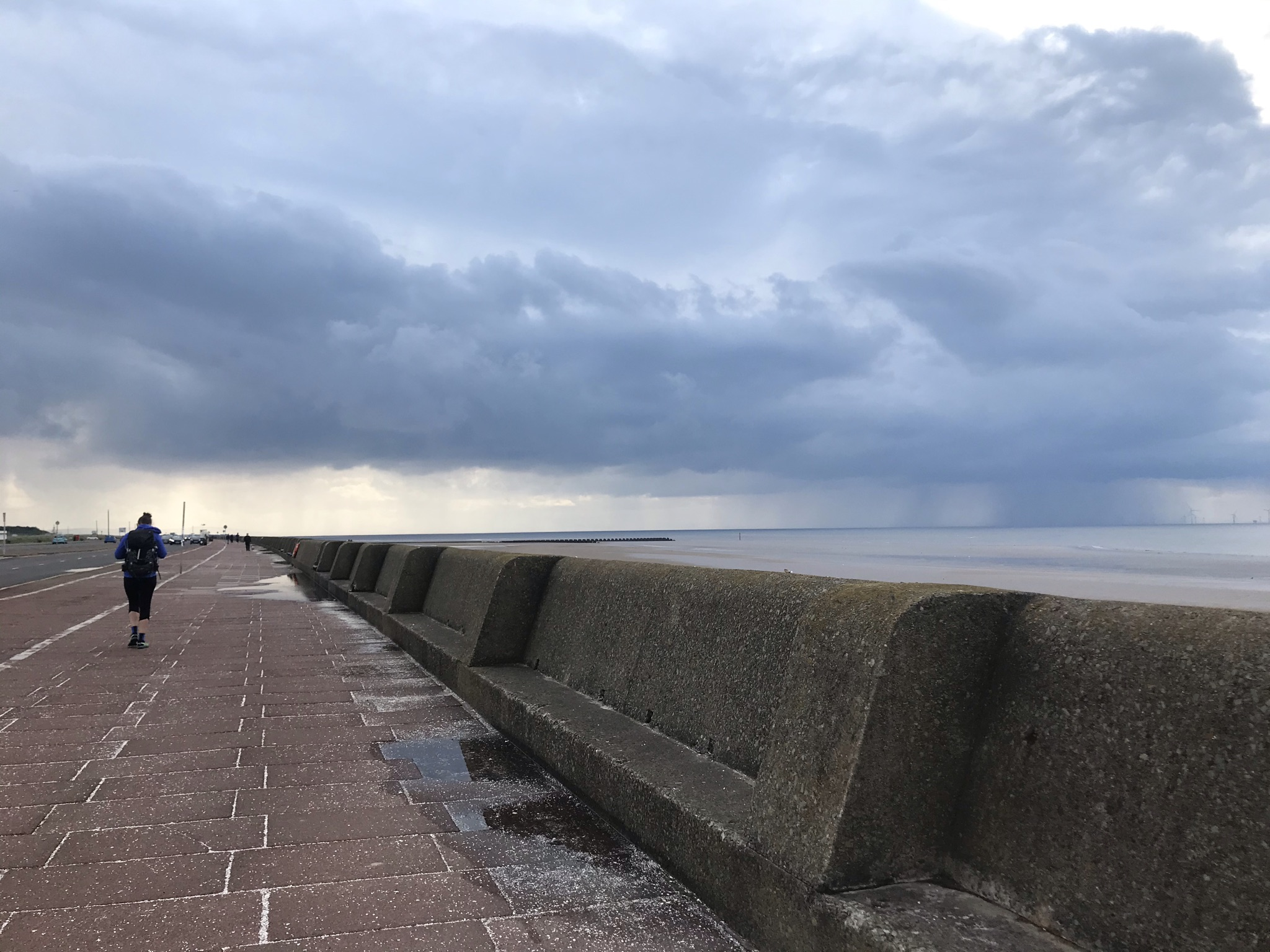 Sarah walking away from the camera along an empty promenade with a sea wall. In the far distance there is heavy rain