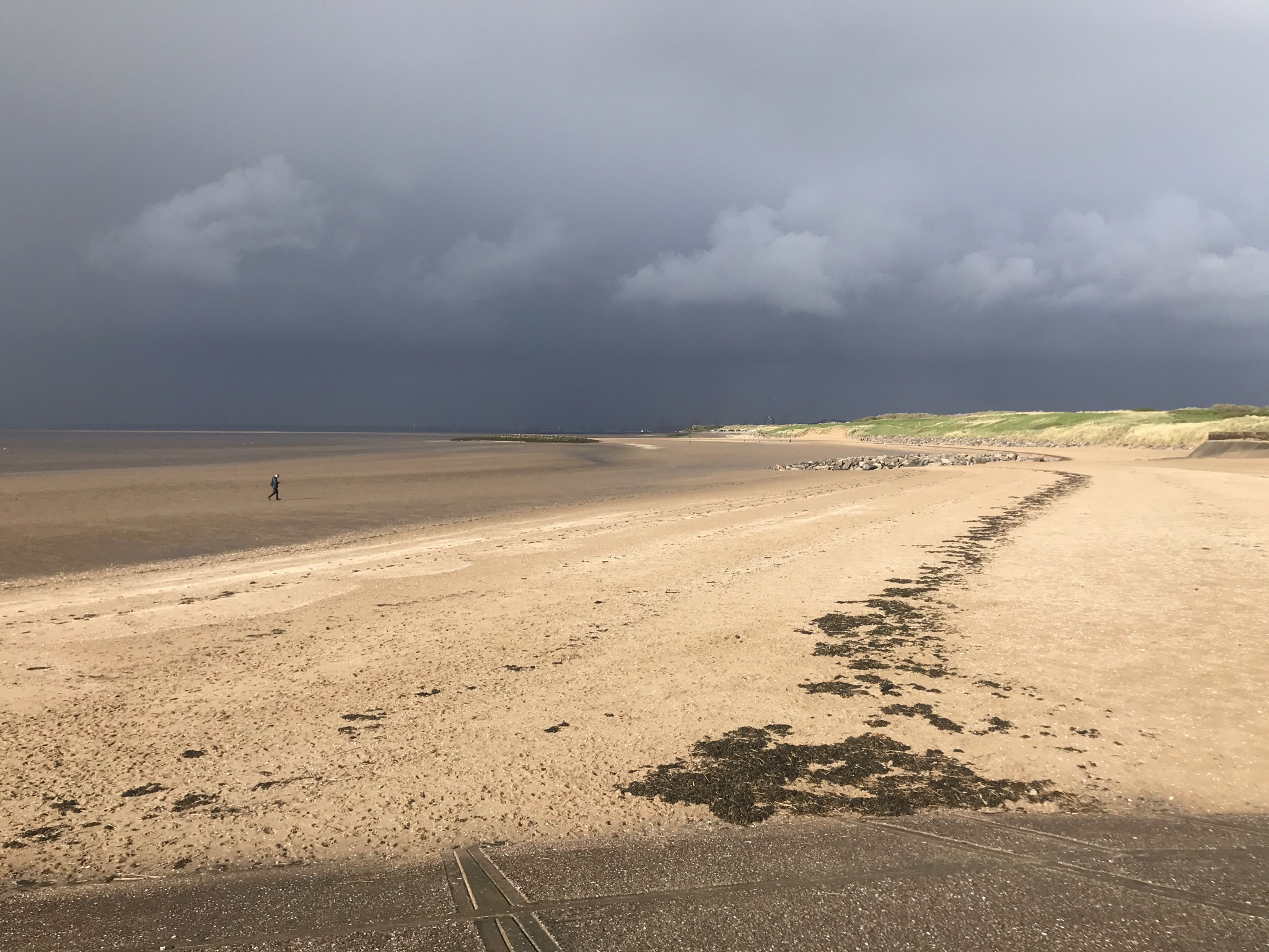 A wide sandy beach with a single person walking in the distance. The sky is dark with rain clouds