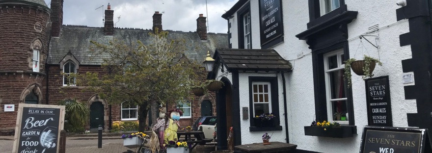 A black and white pub with two scarecrows on a bike outside.