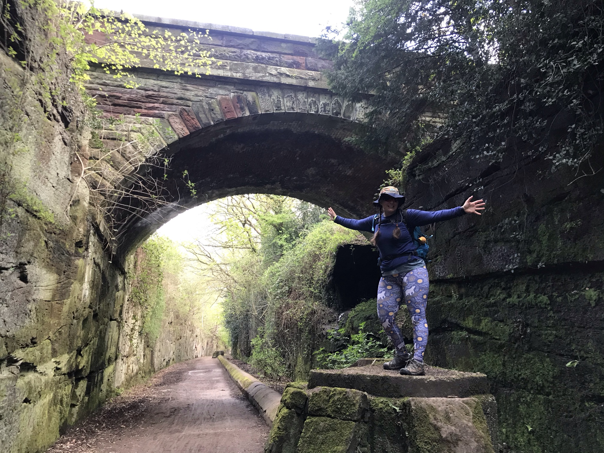 Ellen stands posing on a stone structure. The path is a disused railway in a deep cutting in the rock. Behind her is a bridge over the cutting
