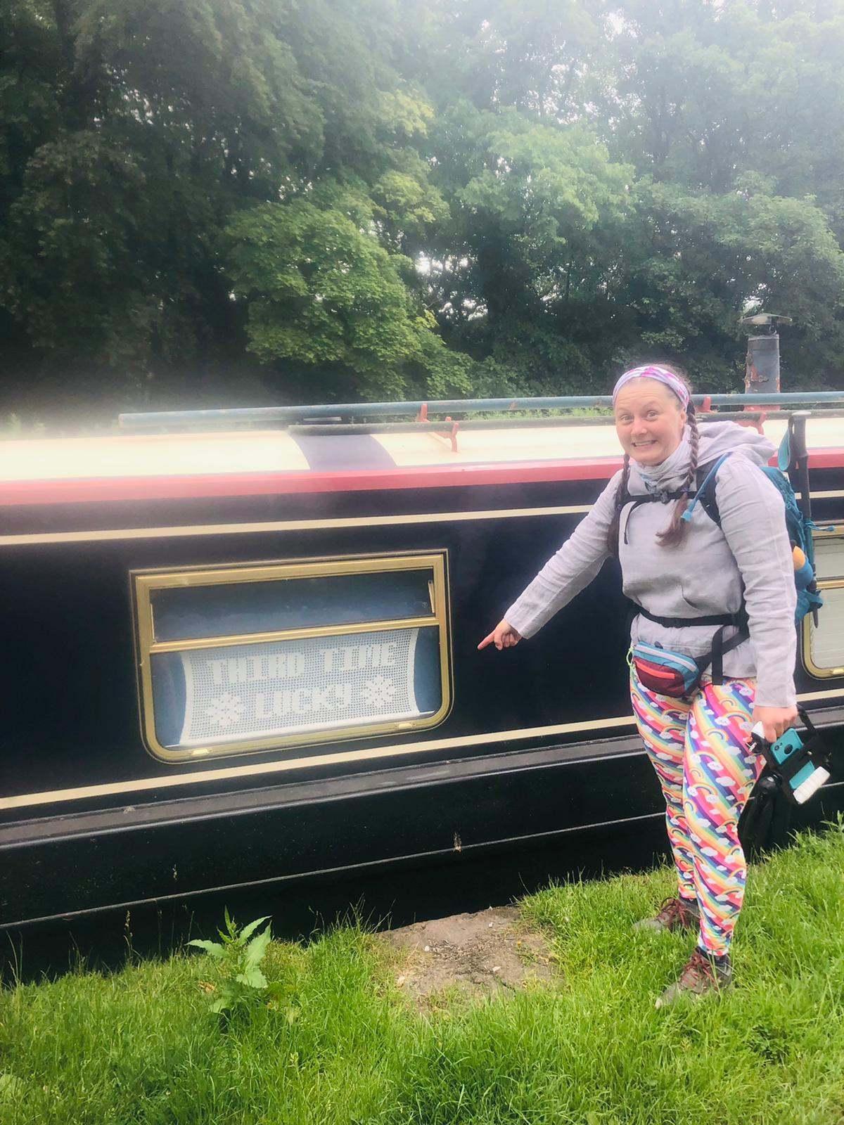 """Ellen grins at the camera pointing to a lacework sign hanging in a narrowboat window that says """"third time lucky"""""""