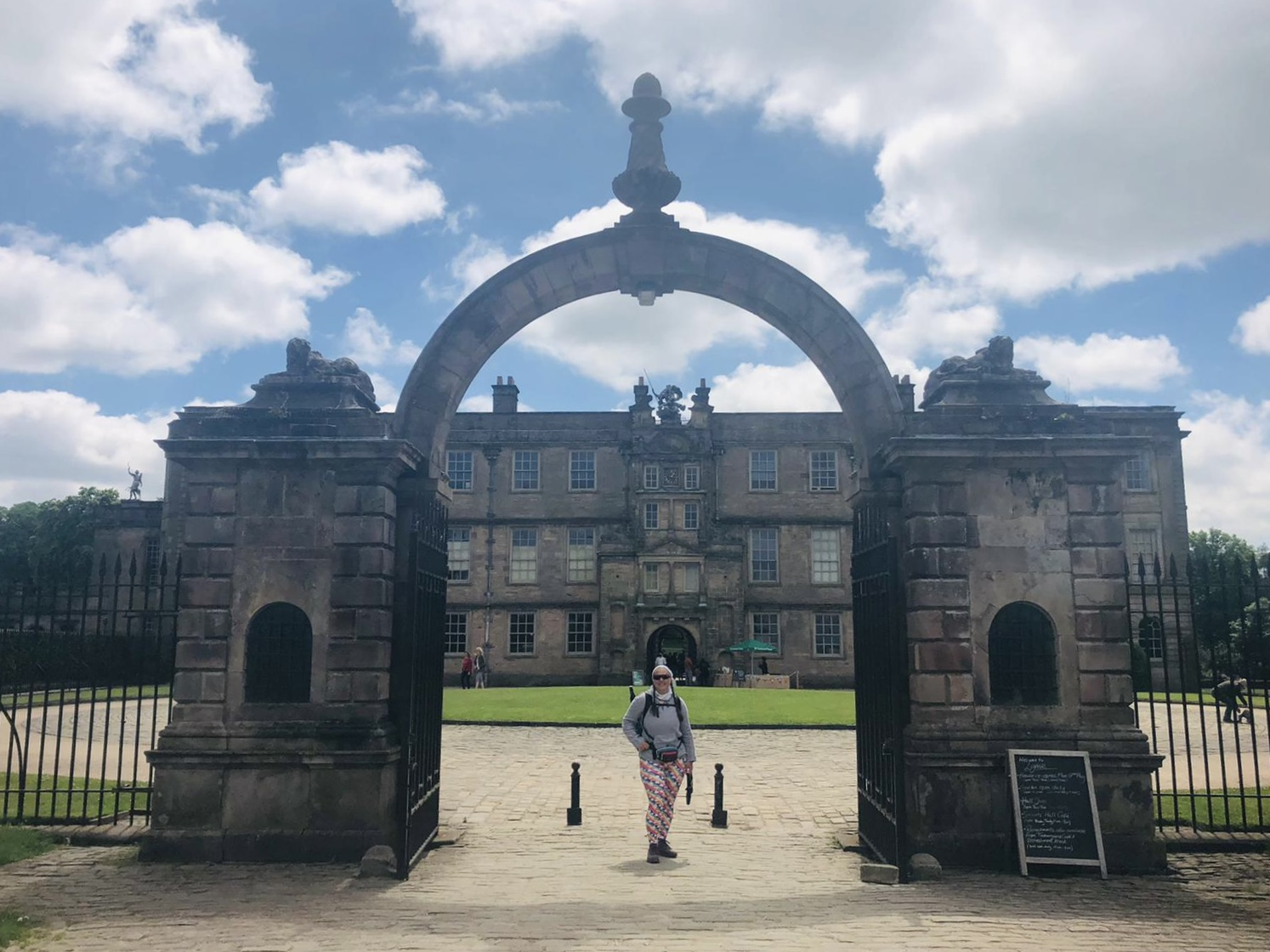 Ellen stands under an large stone archway at the entrance to Lyme house.