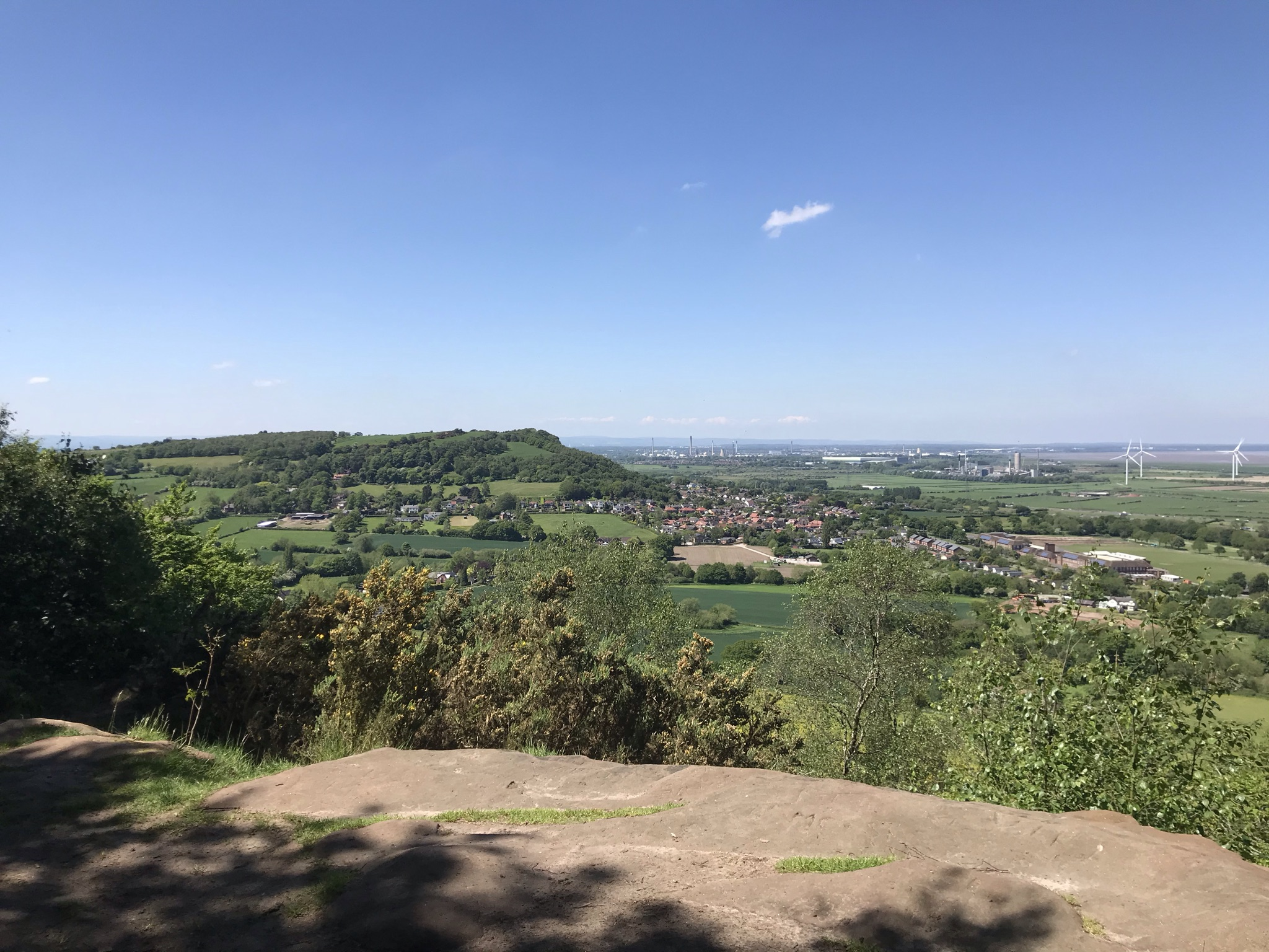 A rock ledge about the trees looing to the wooded Helsby Hill. There are wind turbines and one tiny cloud