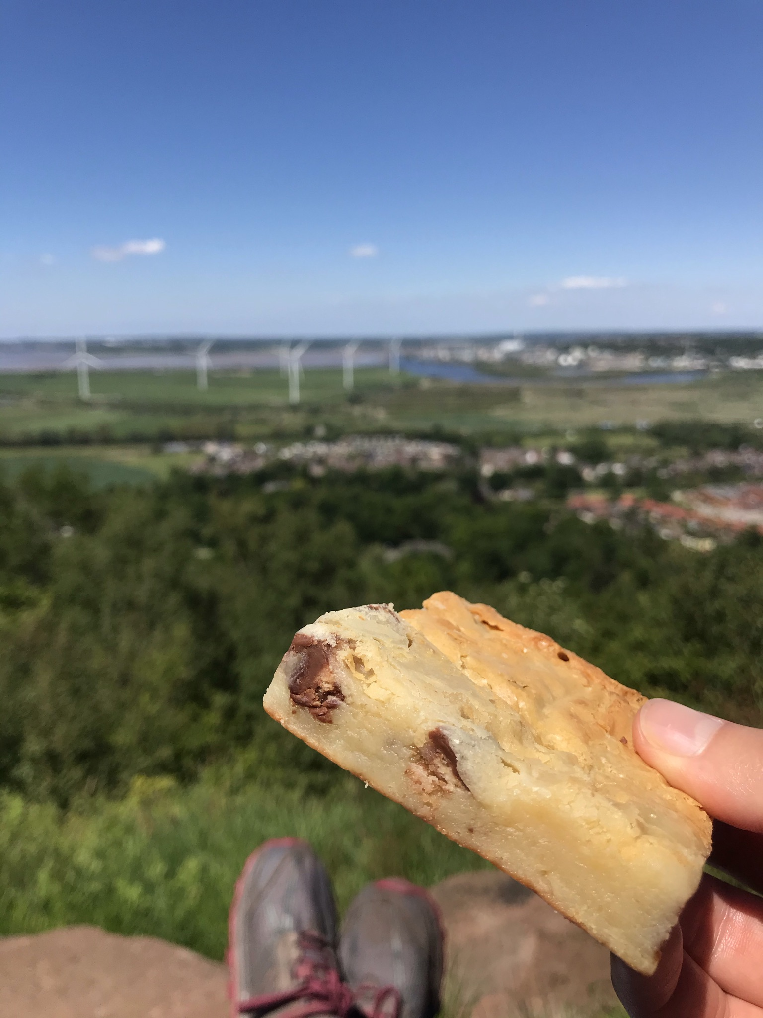 A blondie cake is held up to the camera. The background of feet resting on the stone, trees and distant wind turbines is blurred