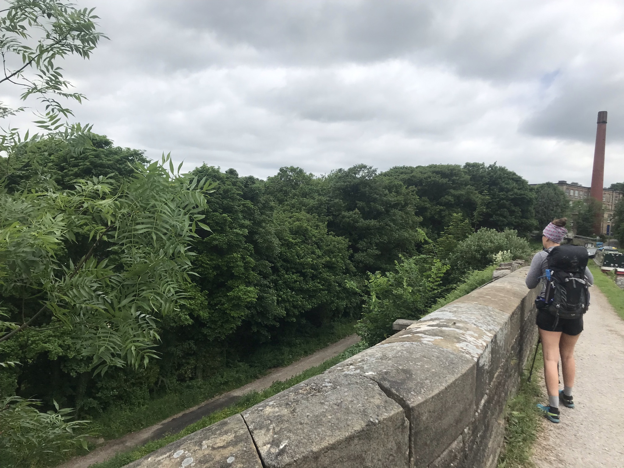 Sarah stands with her back to the camera looking over a wide stone parapet. There is a tall brick chimney and canal boats in the distance.