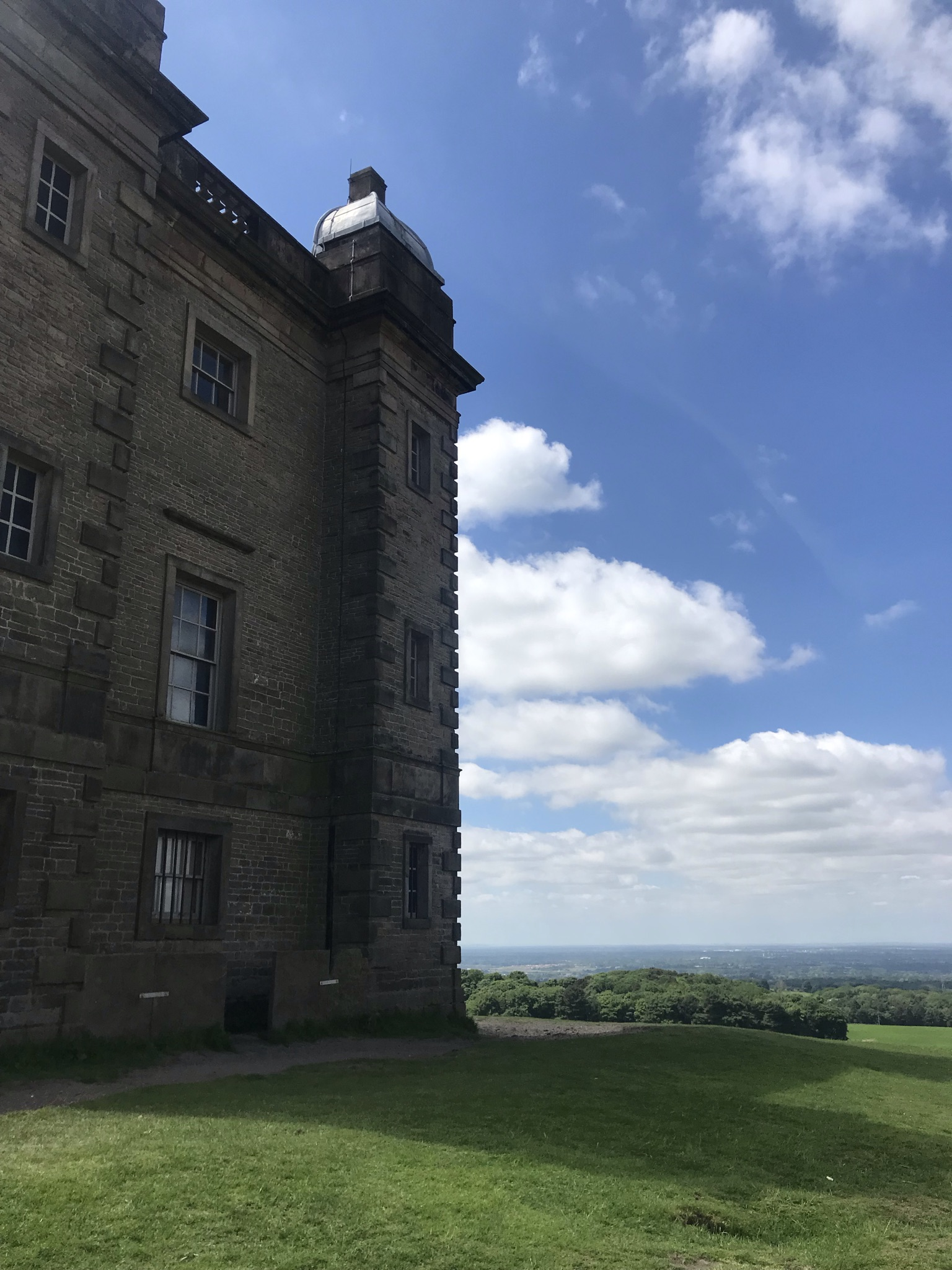 A stone 18th century three story building surrounded by short grass slopes. The sky is blue with white clouds and long views over the Cheshire plains