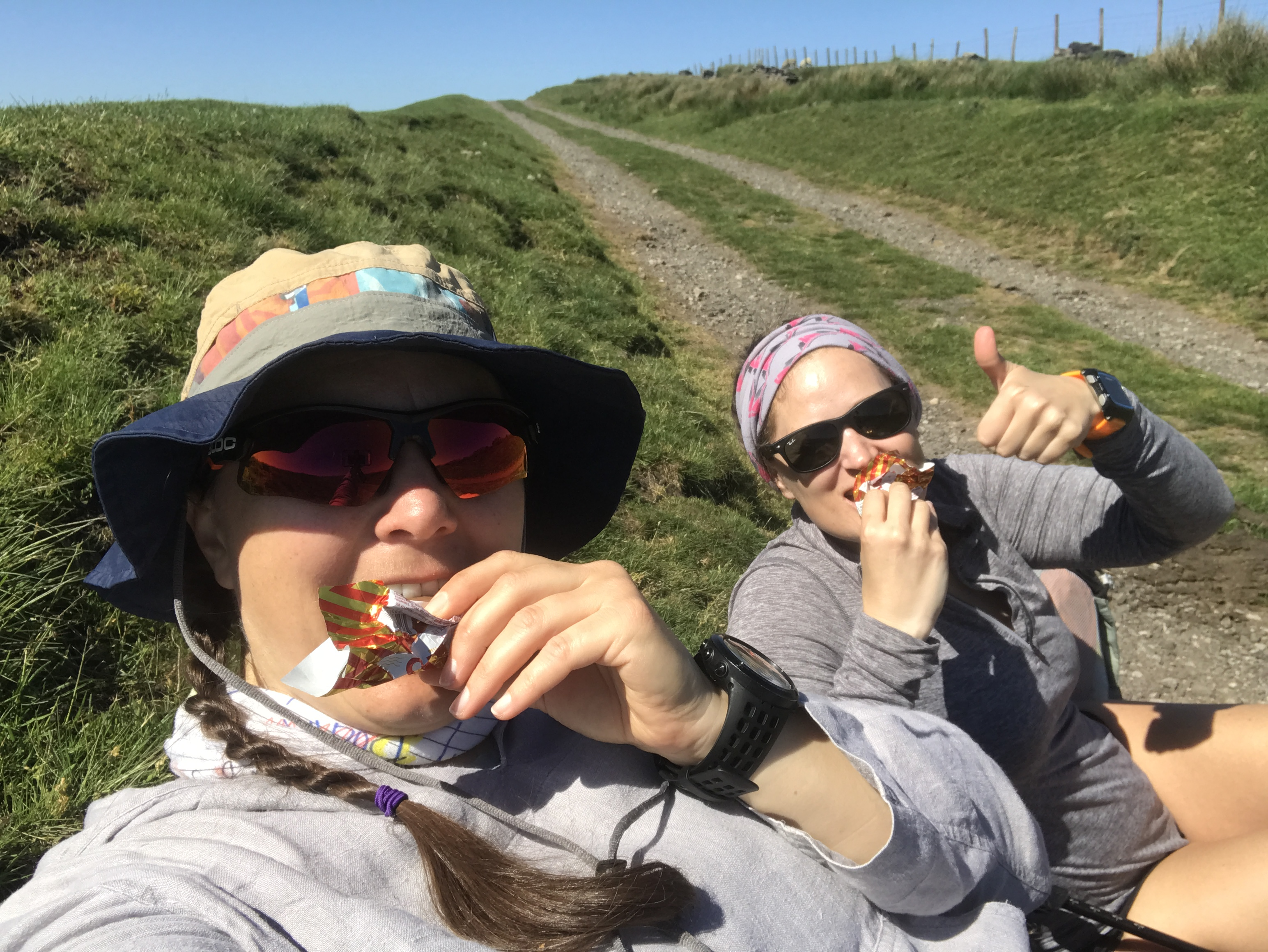 A selfie of Ellen and Sarah sat on a grass bank eating Tunnock's caramel wafer. Behind them tracks stretch up to a blue sky