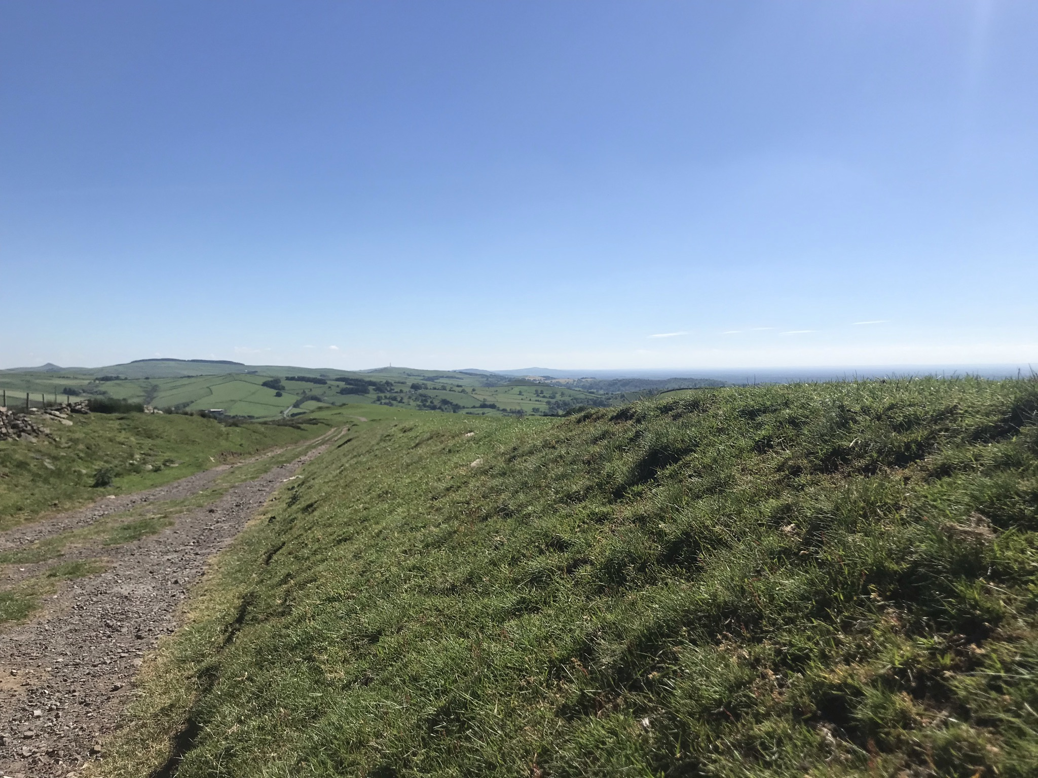 Clear blue sky above a stony track heading gently down hill between soft grassy banks. Hill can be seen on the horizon