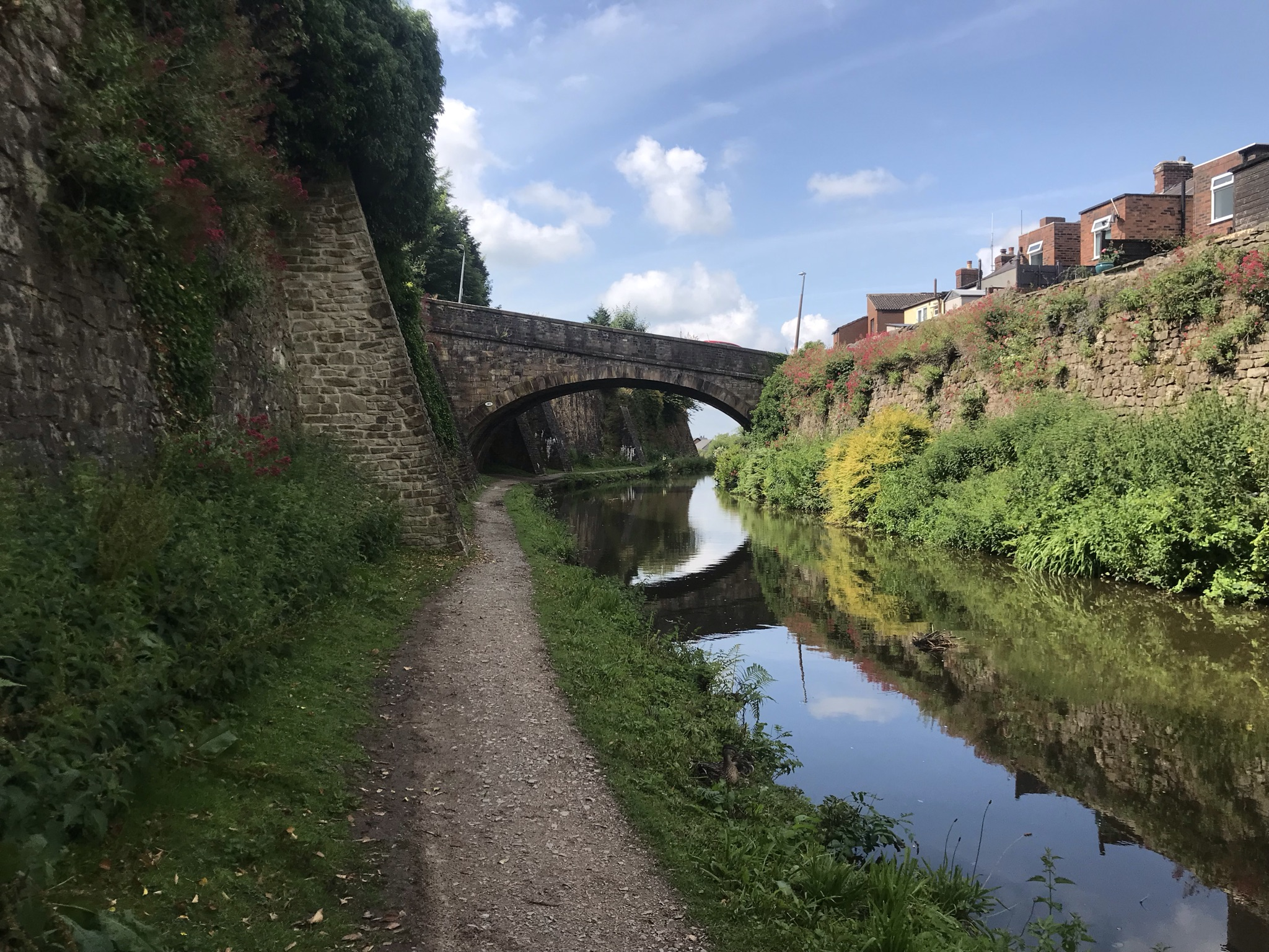 A towpath along the canal with high, flower covered stone walls either side. The canal is still and reflecting the walls and the sky