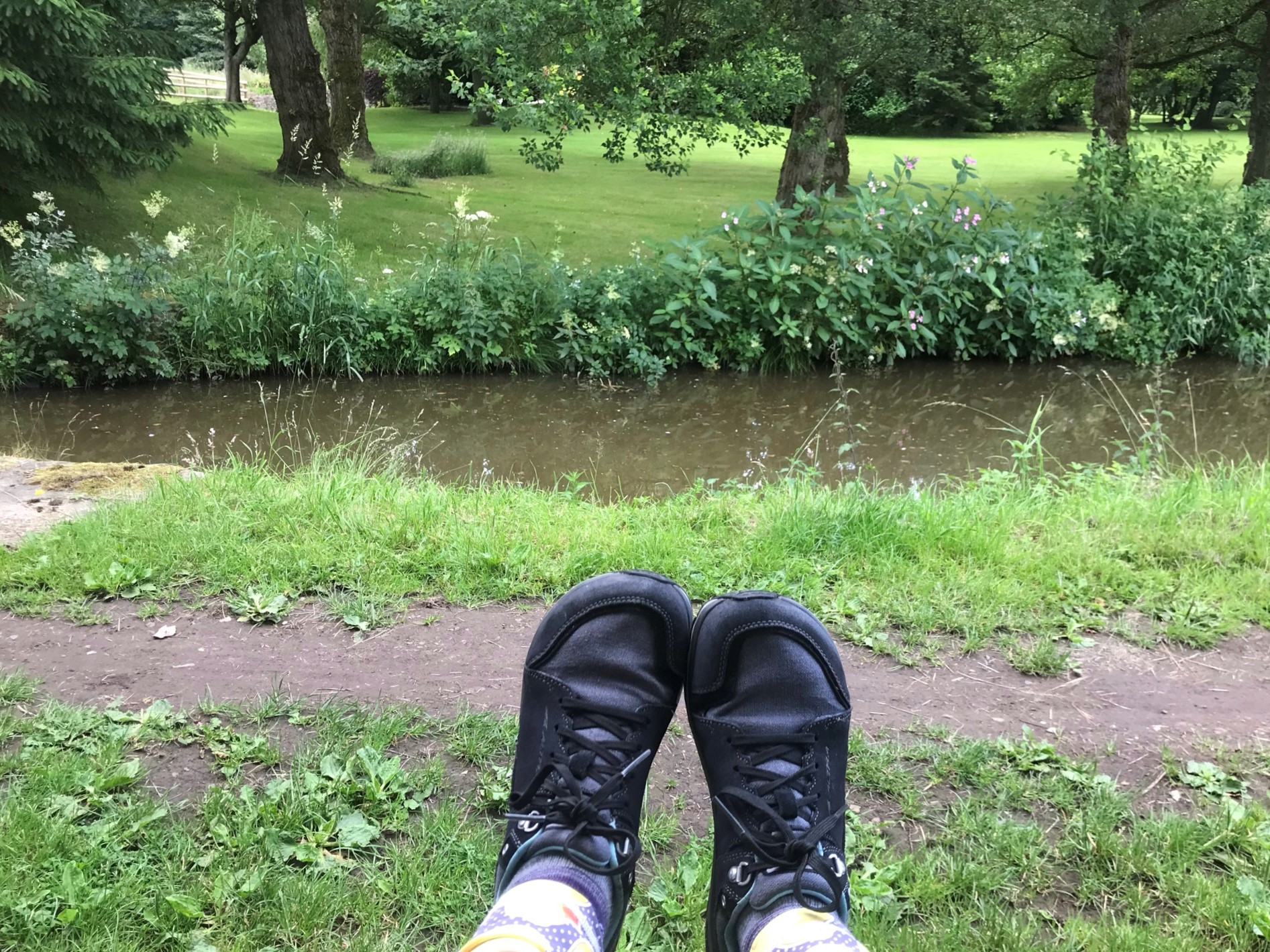 Feet with grey lace up walking shoes held up with the canal and neat mown grass on the far bank