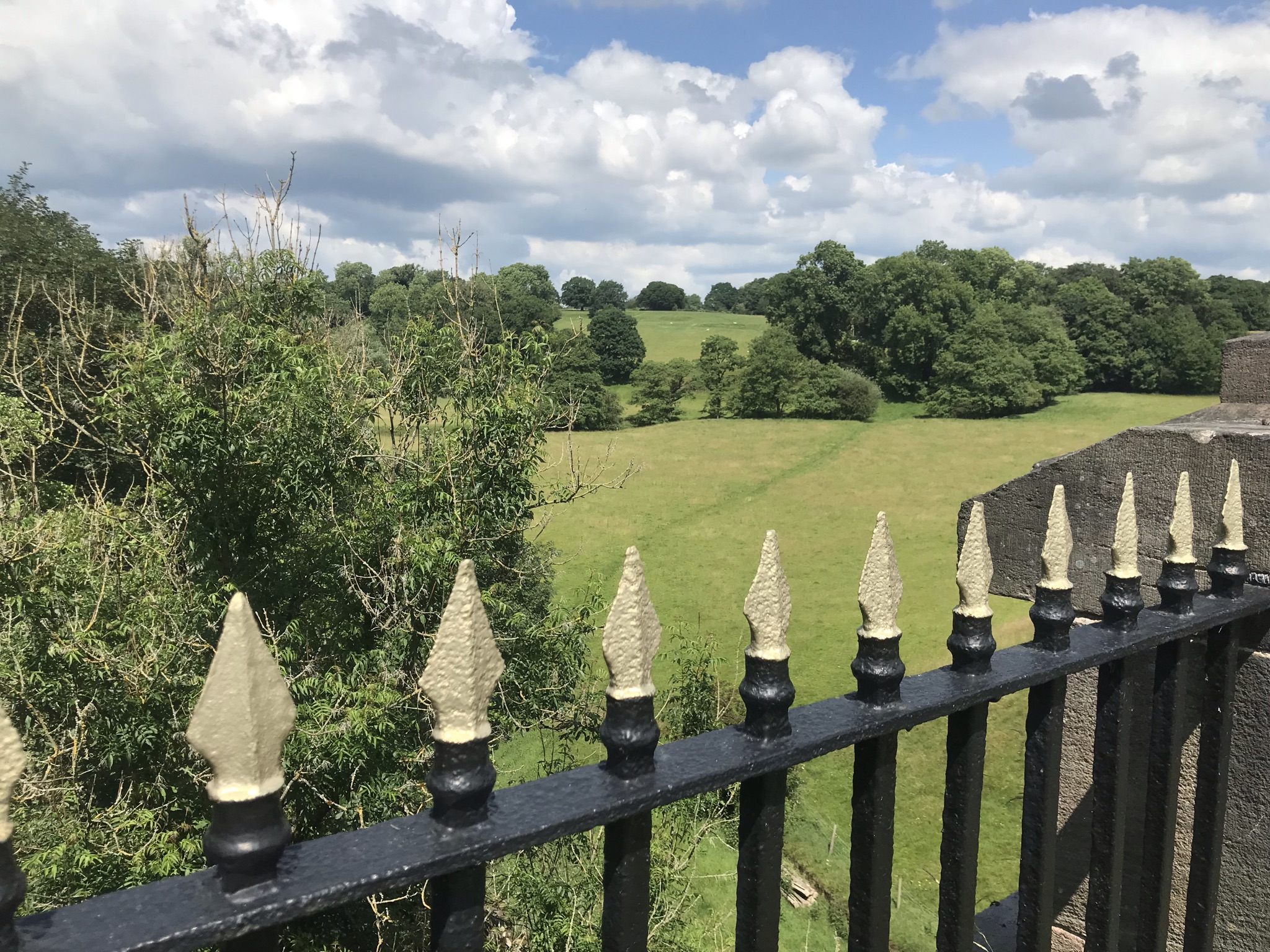 Gold and black railings overlooking a long drop to green fields and trees, with fluffy clouds in the sky