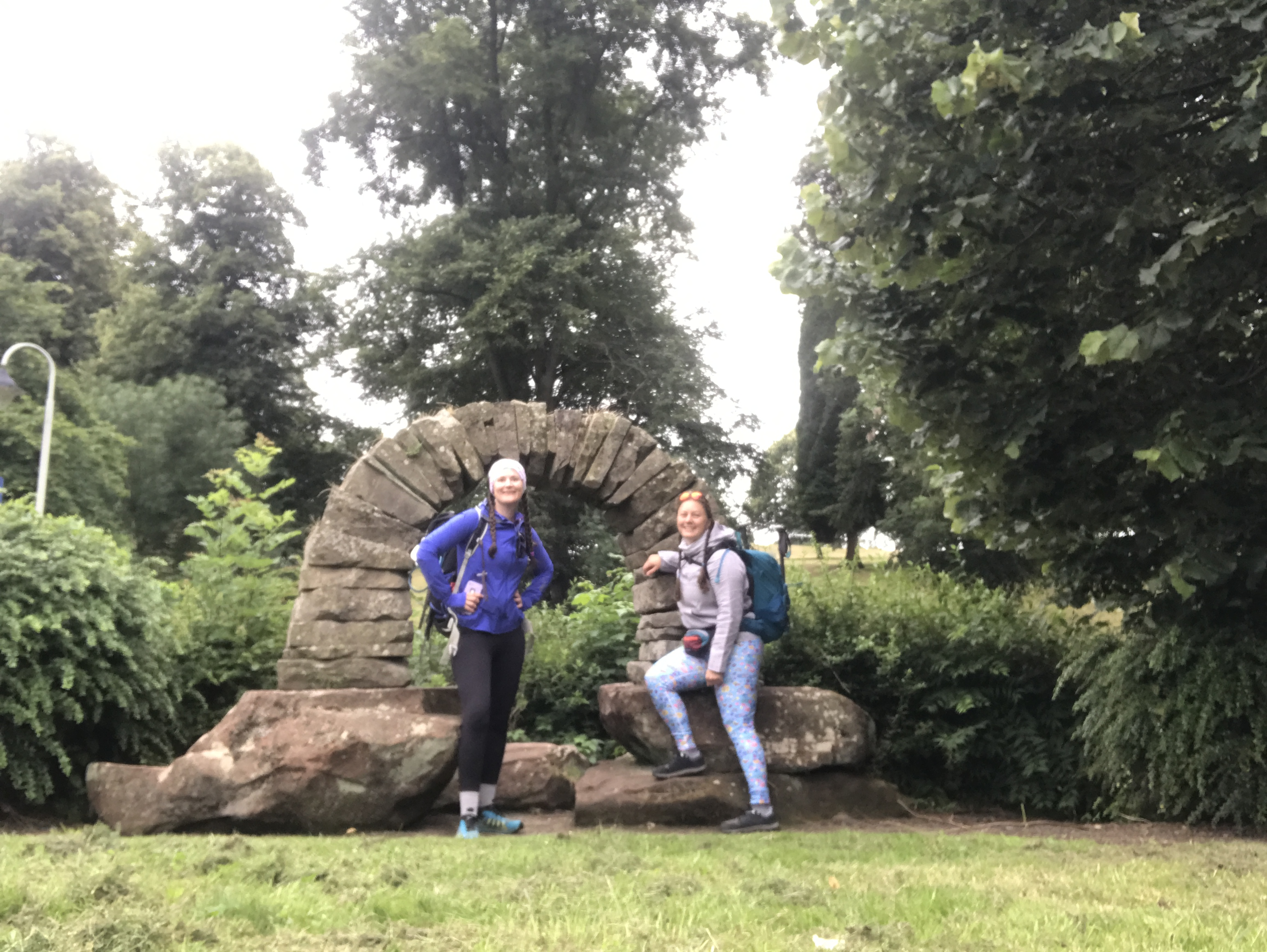 Sarah and Ellen stand in front of a standstone arch