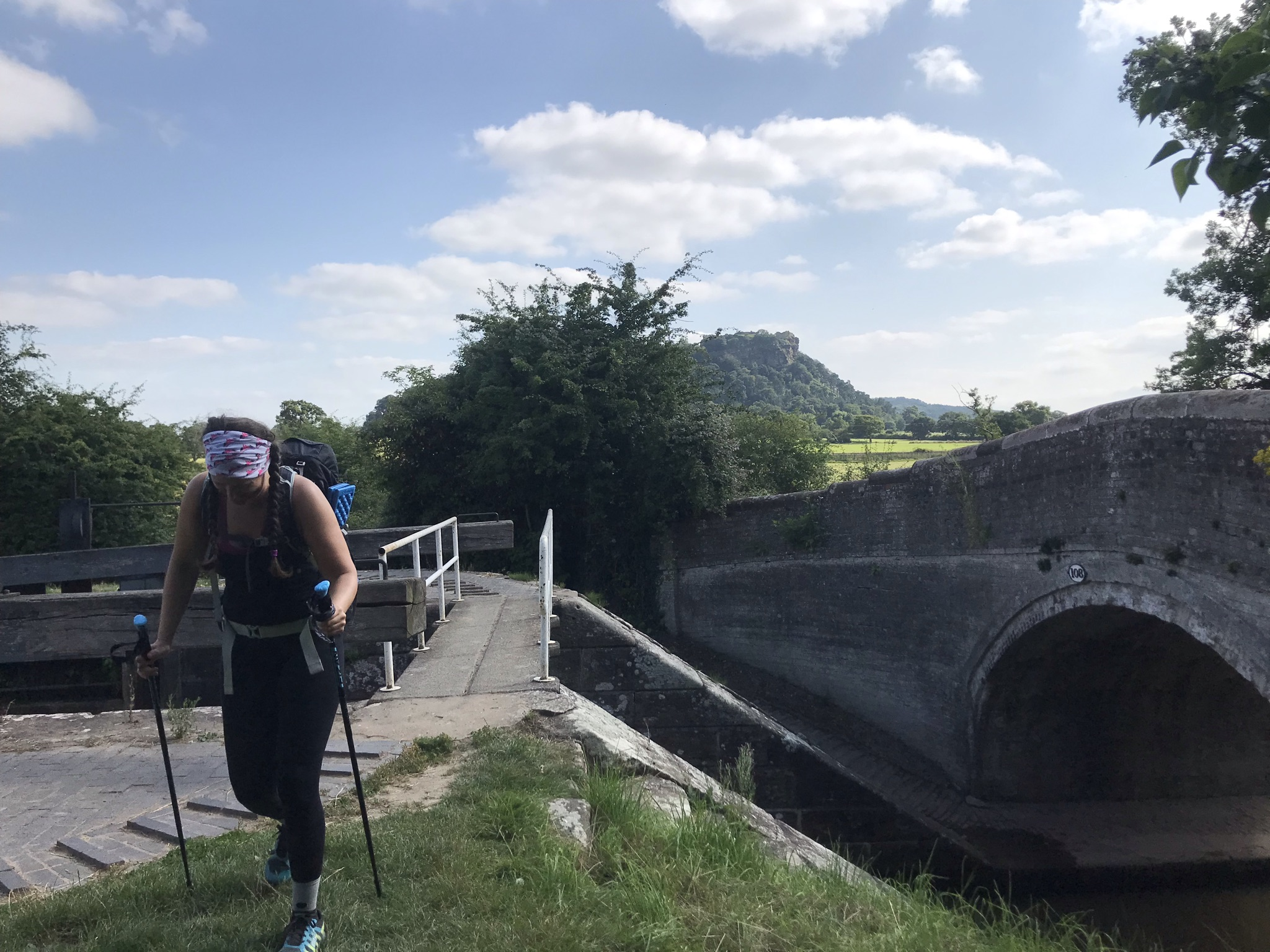 Sarah, walking with poles crosses a narrow bridge over a lock. Beeston Castle is in the distance